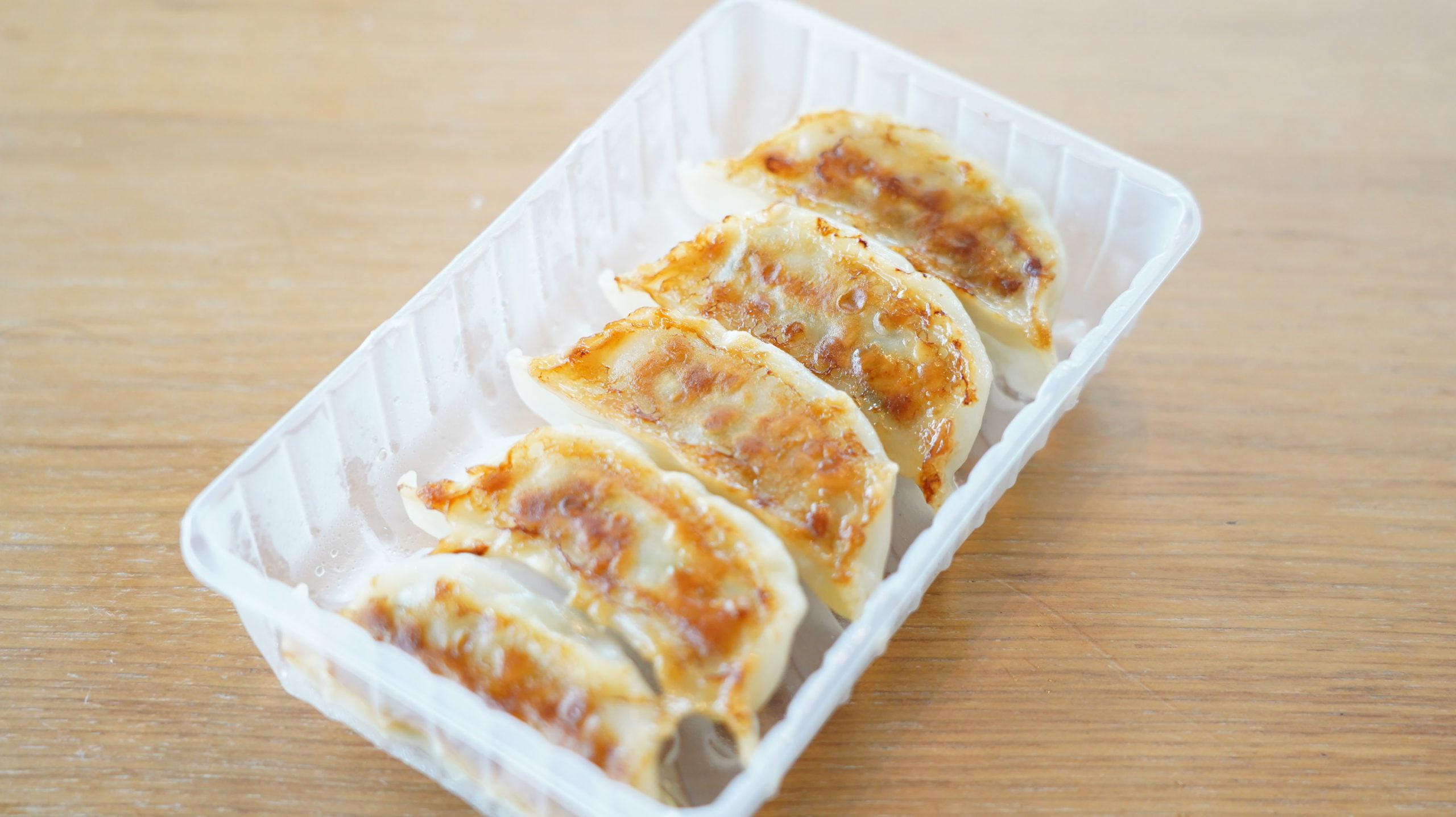 セブンイレブンの冷凍食品「国産お肉と野菜の焼き餃子」でトレーのまま食べられる様子の写真