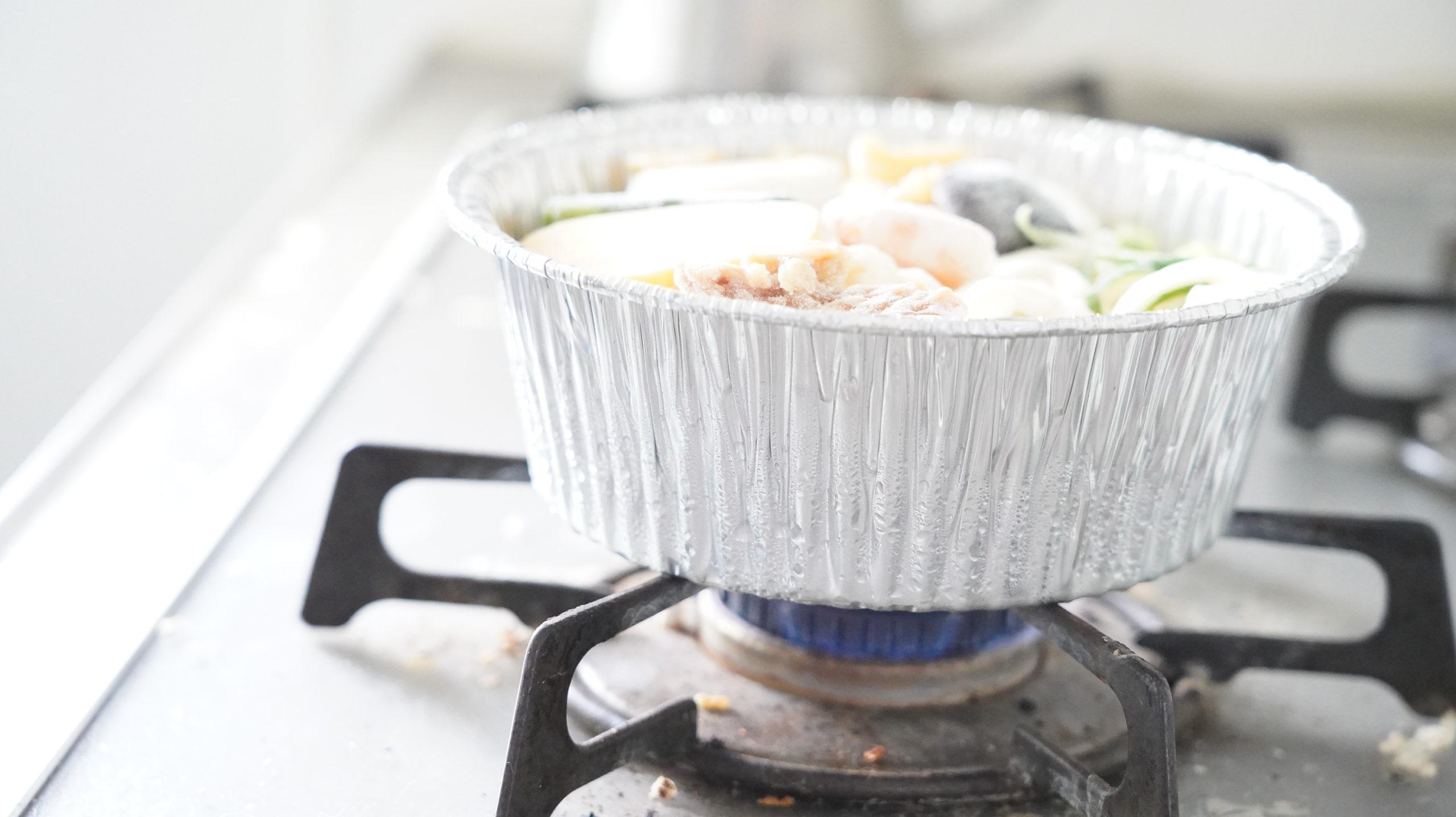 セブンイレブンの冷凍食品「関西風だし・鍋焼うどん」をガスコンロで加熱している写真