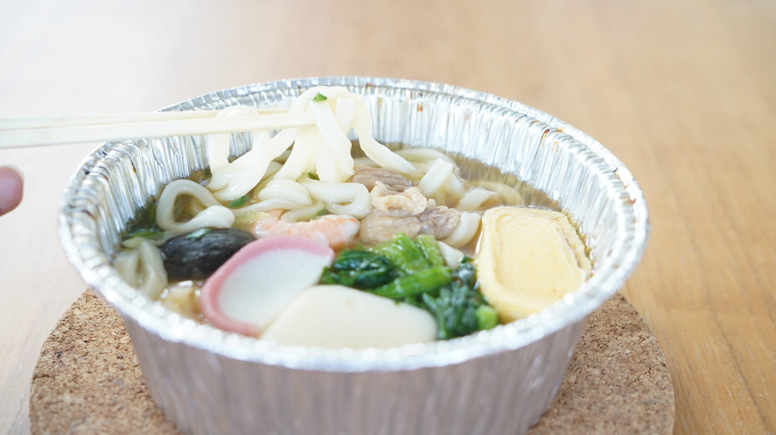 セブンイレブンの冷凍食品「関西風だし・鍋焼うどん」の麺をつまんでいる写真