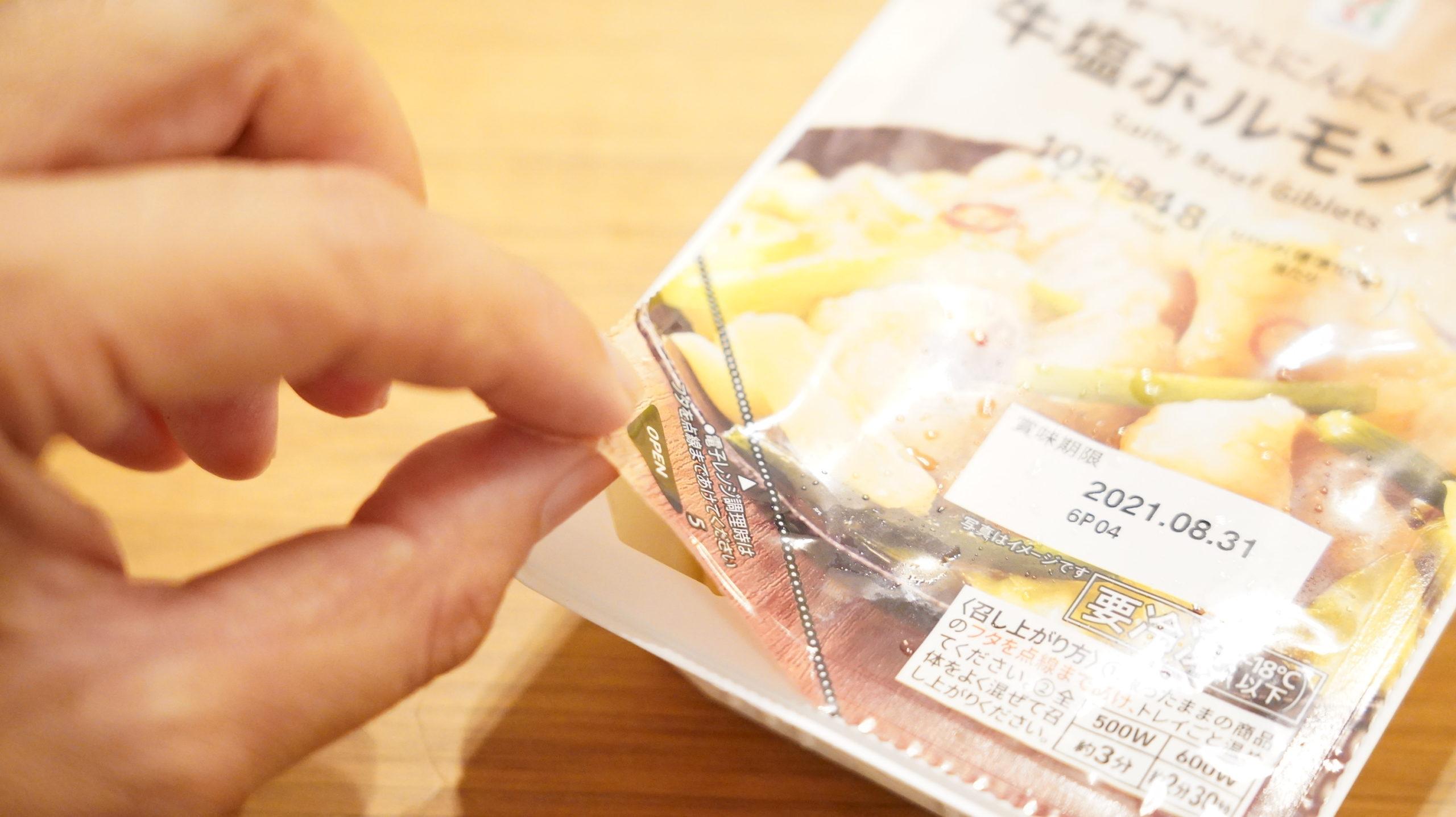 セブンイレブンの冷凍食品「キャベツとにんにくの芽入・牛塩ホルモン炒め」のフタの点線まではがしている写真