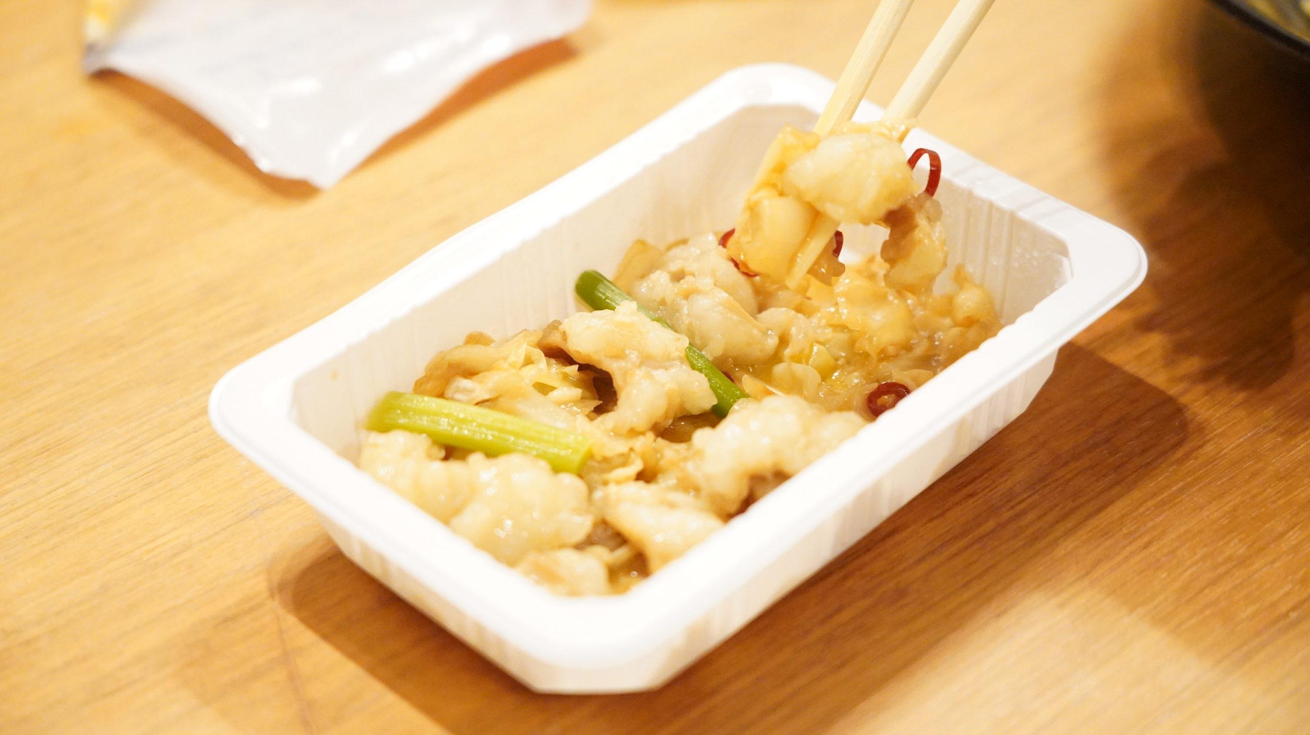 セブンイレブンの冷凍食品「キャベツとにんにくの芽入・牛塩ホルモン炒め」を箸で掴んでいる写真
