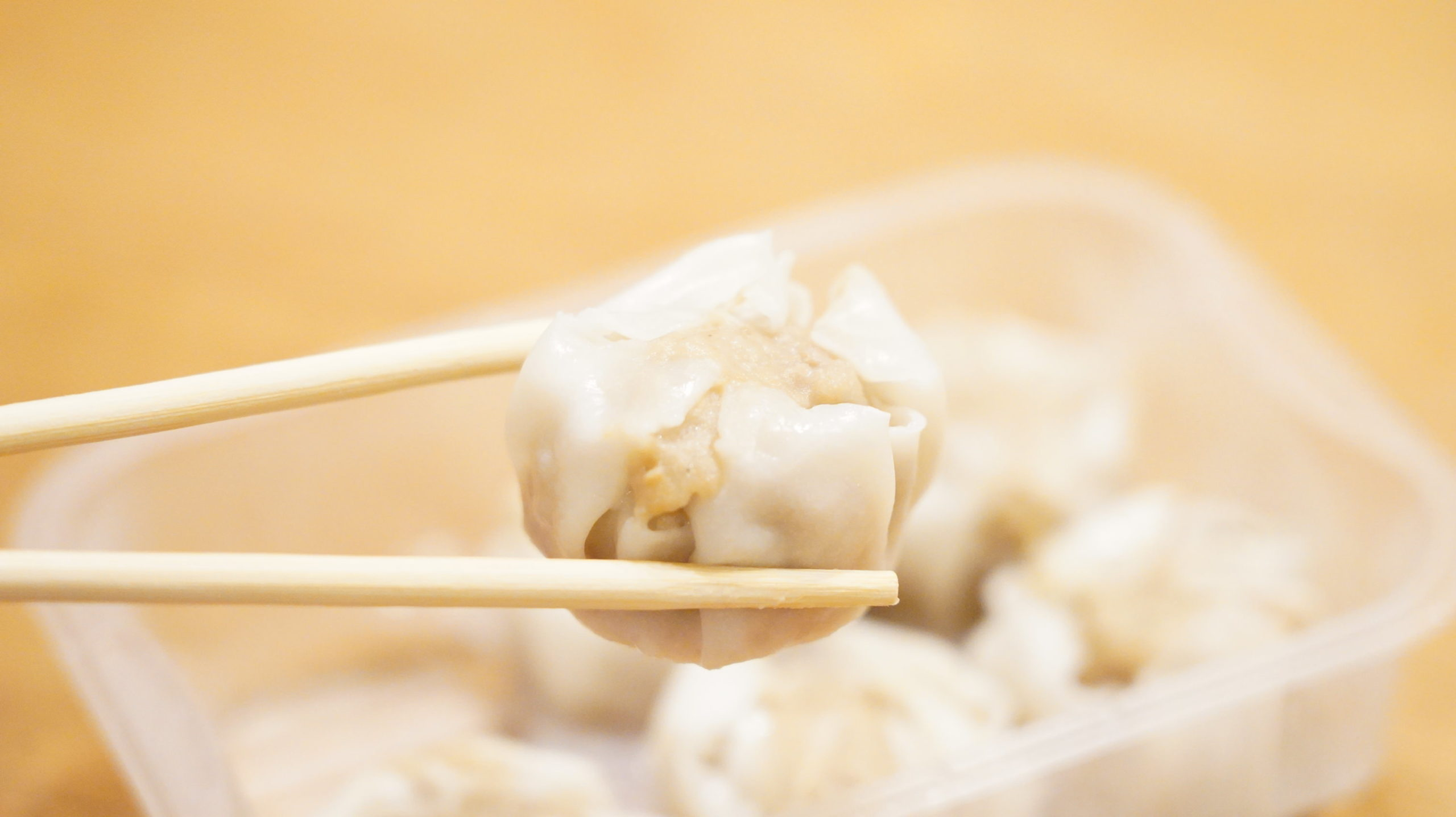 セブンイレブンのおすすめ冷凍食品「特製点心・本格肉焼売」を箸でつまんでいる写真