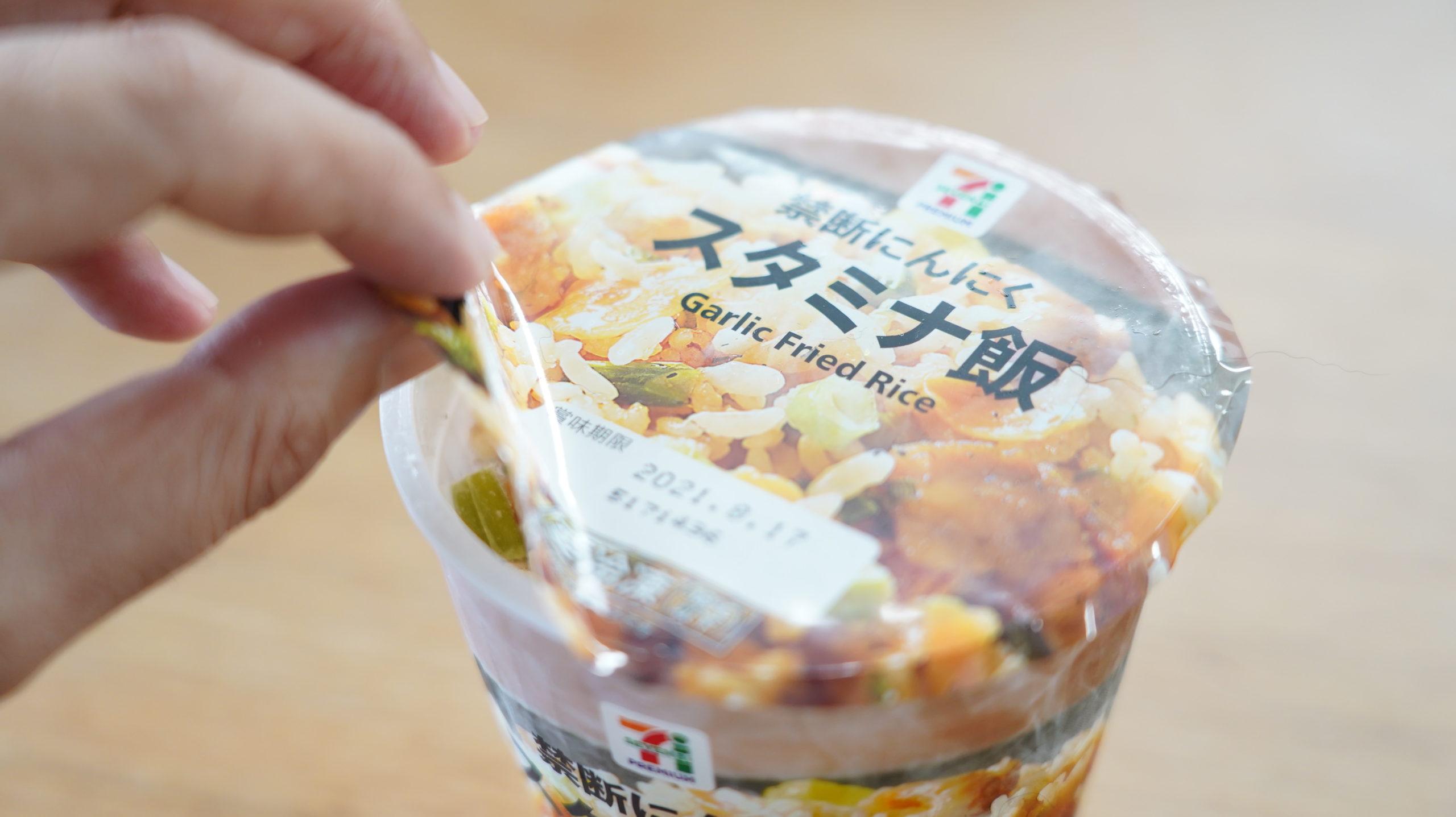 セブンイレブンの冷凍食品「禁断にんにくスタミナ飯」のフィルムを点線まではがしている写真