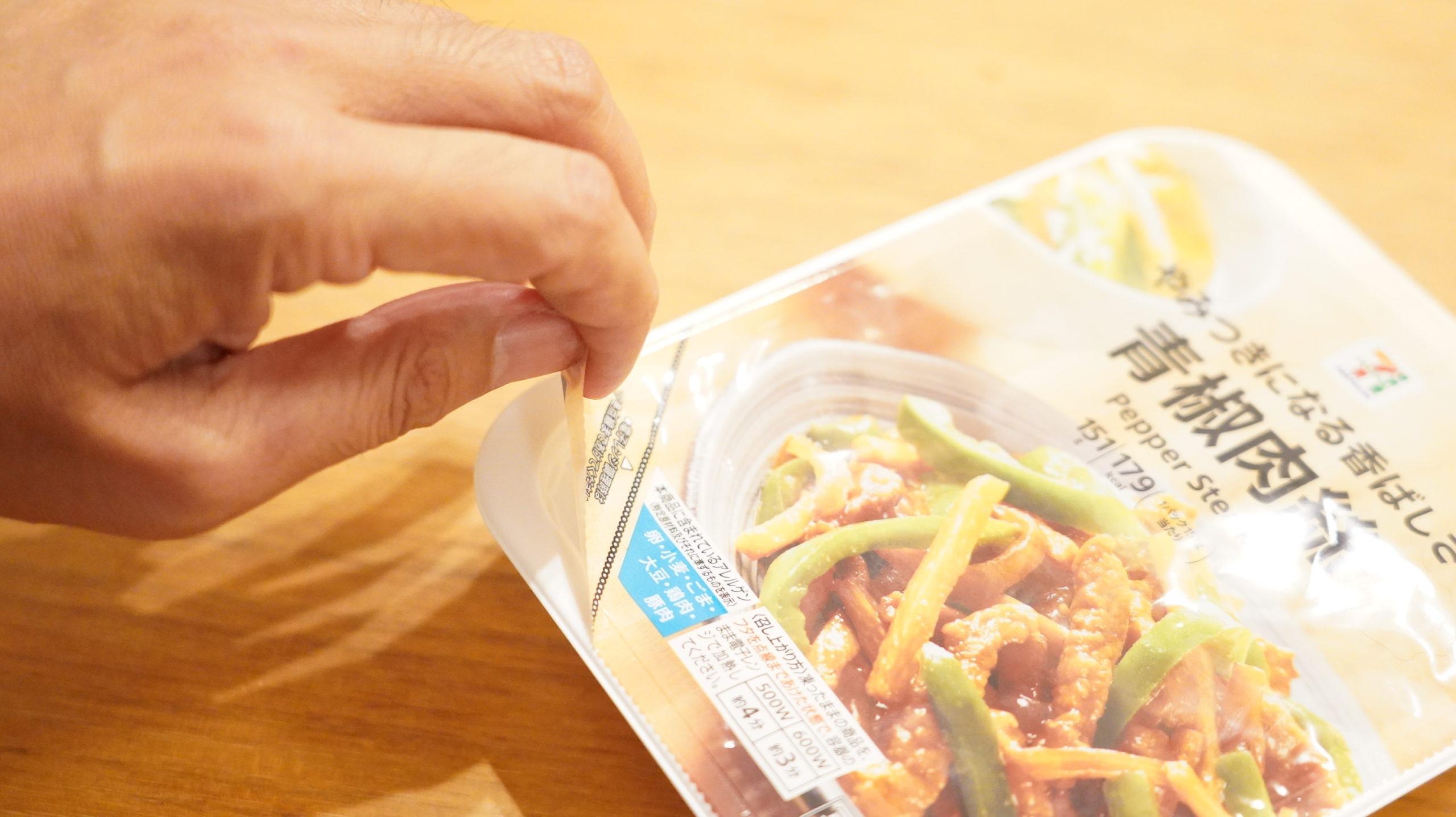 セブンイレブンの冷凍食品「やみつきになる香ばしさ・青椒肉絲(チンジャオロースー」のフタを点線まではがしている写真