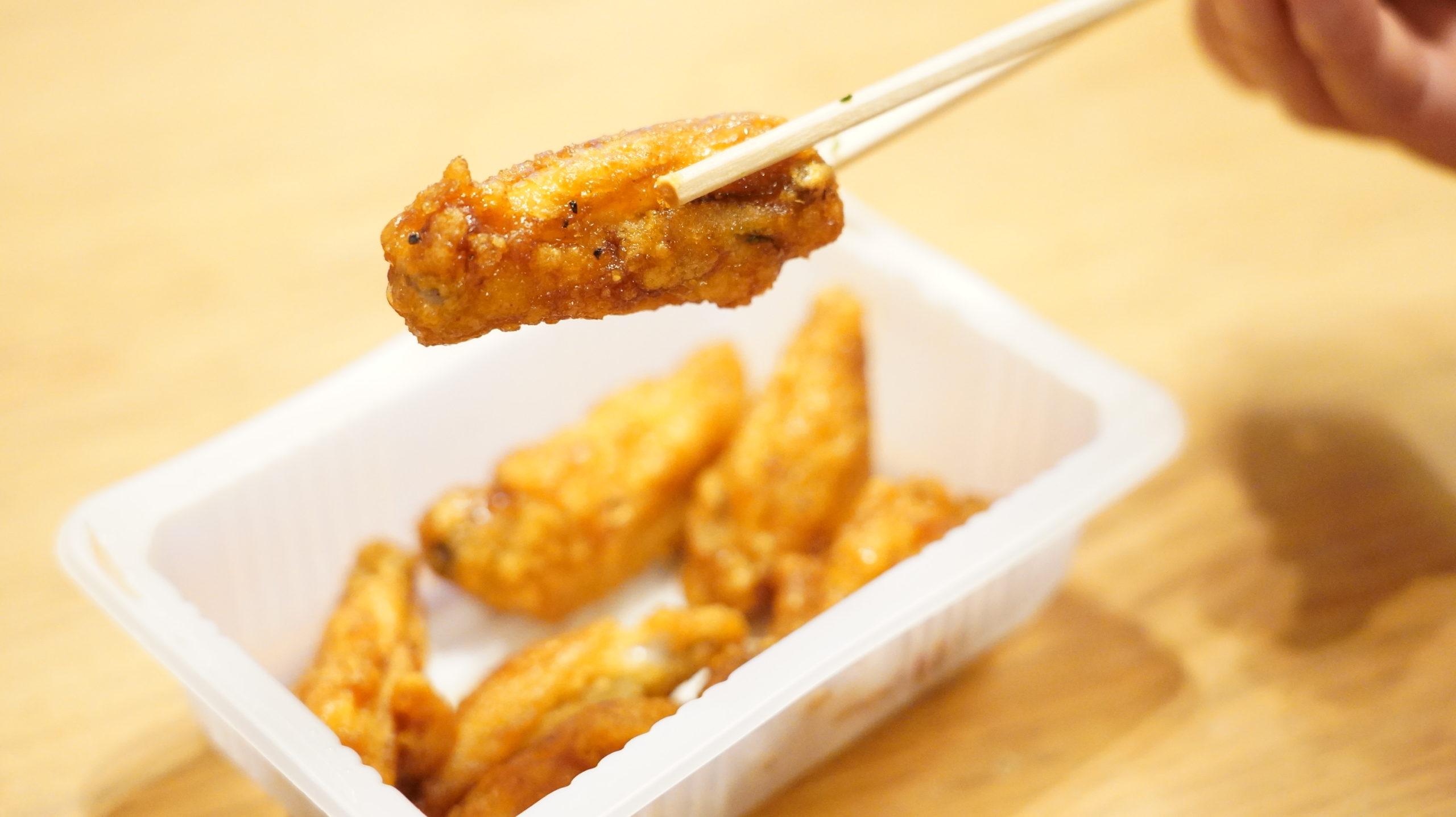 セブンイレブンの冷凍食品「おかずやおつまみに・手羽中唐揚げ」を箸でつまんでいる写真