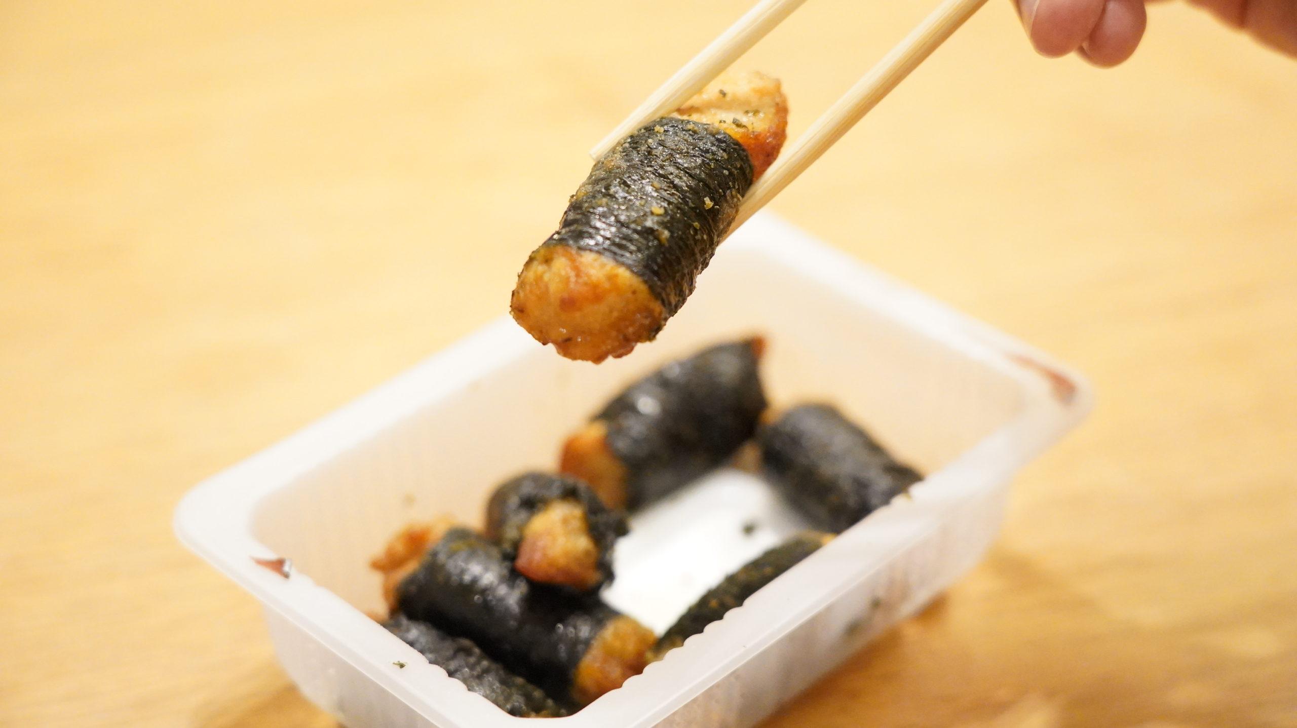 セブンイレブンの冷凍食品「和風にんにく風味・海苔巻きチキン」を箸でつまんだ写真