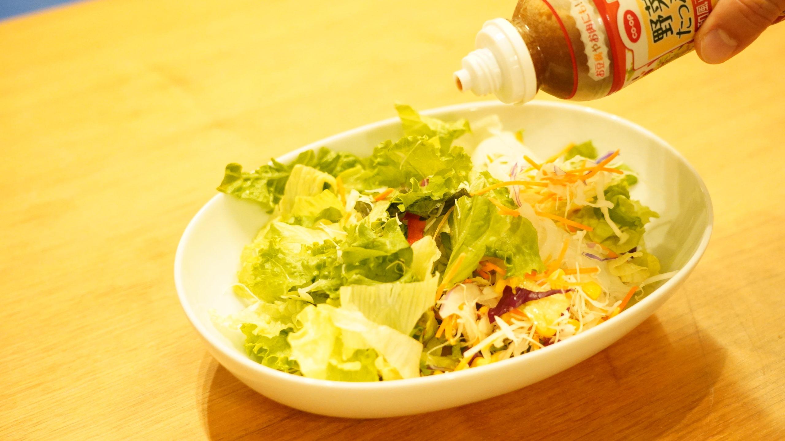 生協の宅配「おうちコープ」の野菜たっぷり和風ドレッシングをサラダにかけている様子