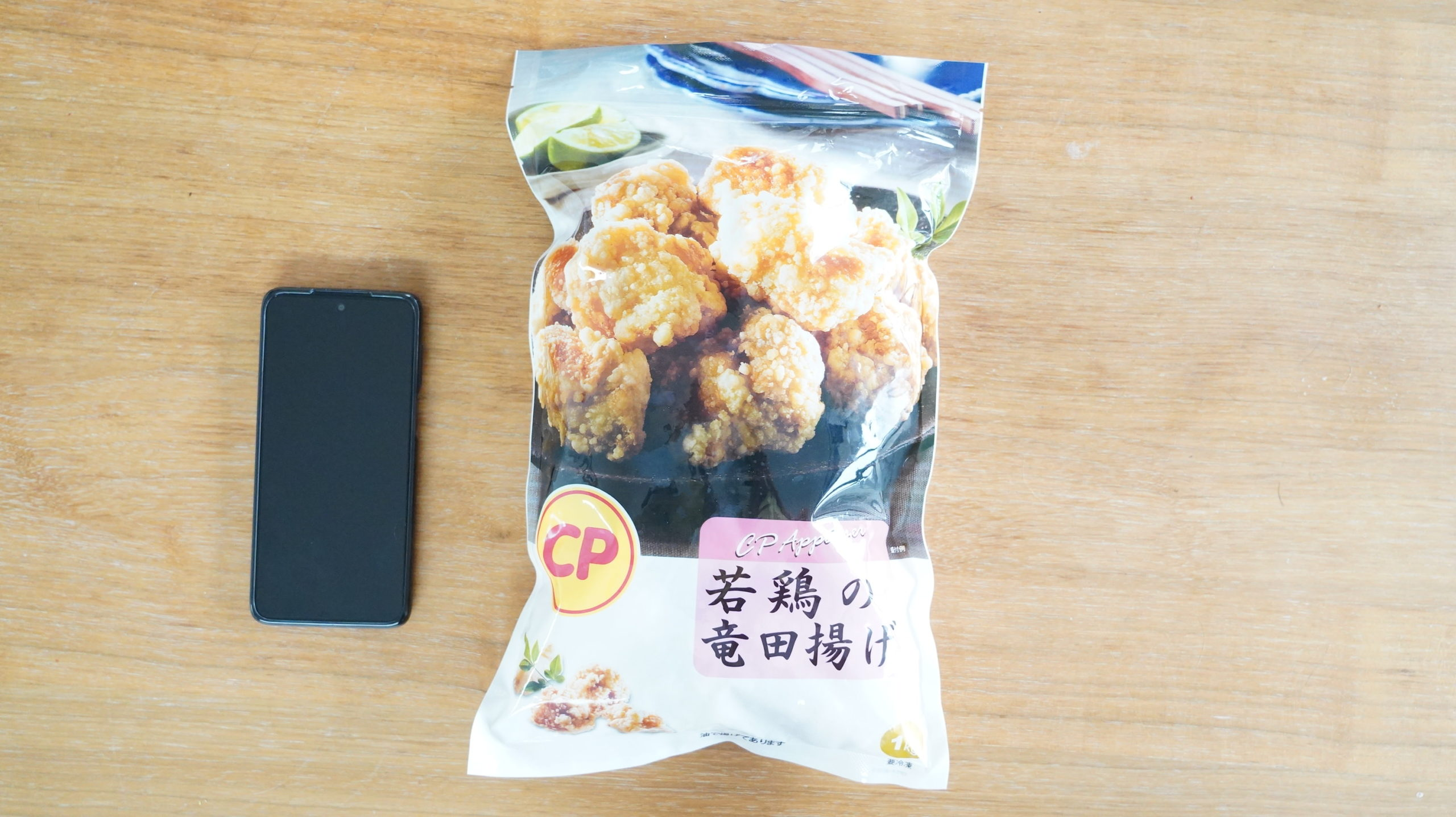 コストコの冷凍食品「CP 若鶏の竜田揚げ」とスマホを比較した写真