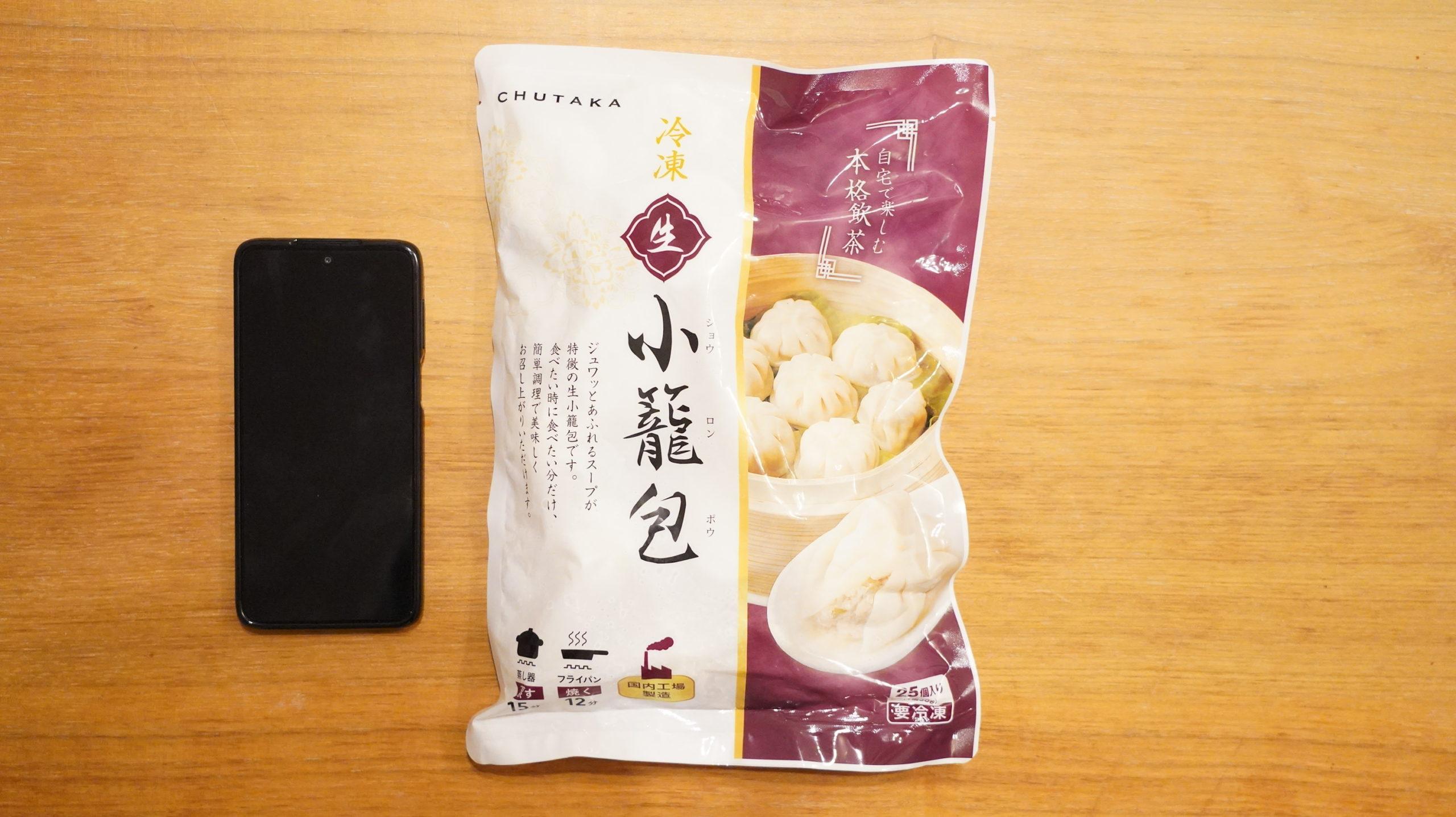 コストコの冷凍食品「冷凍・生・小籠包」のパッケージとスマホの大きさを比較した写真