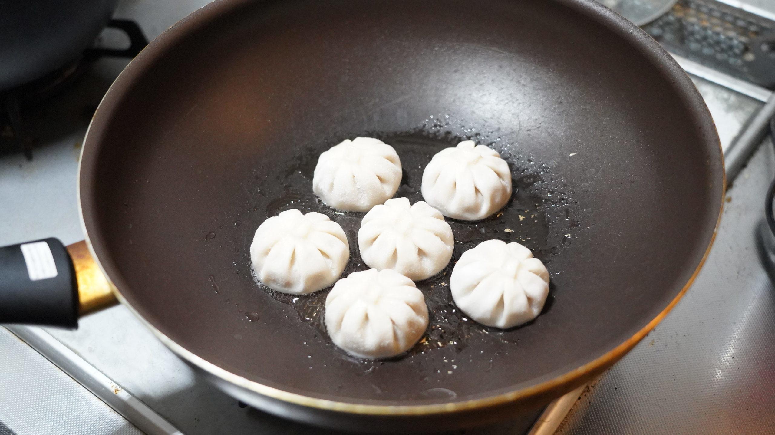 コストコの冷凍食品「冷凍・生・小籠包」をフライパンで加熱している写真