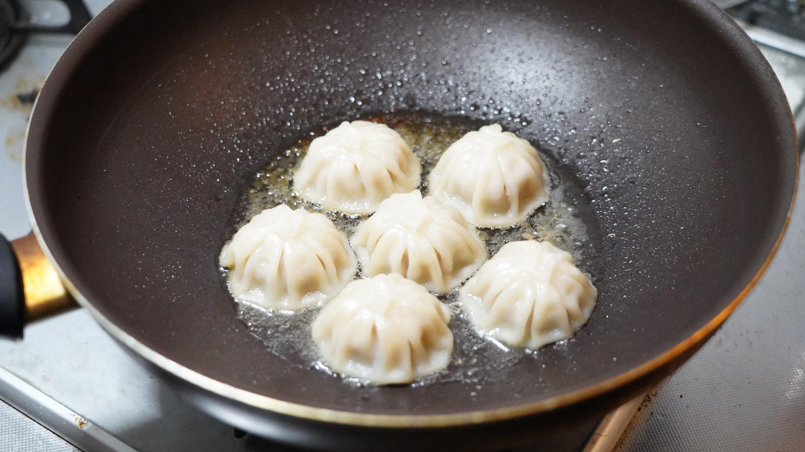 コストコの冷凍食品「冷凍・生・小籠包」をフライパンの蓋を外して加熱している写真
