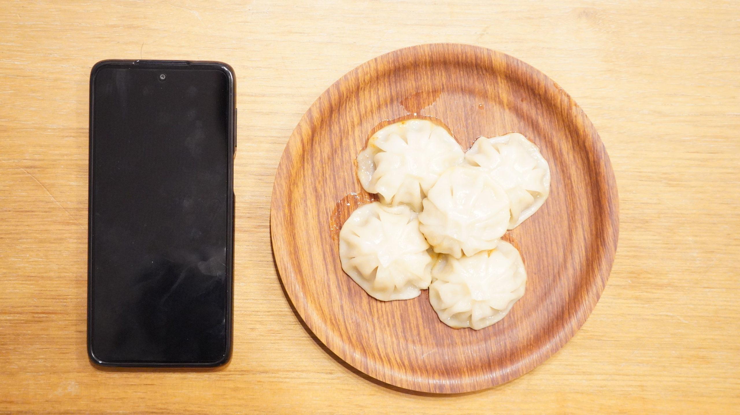 コストコの冷凍食品「冷凍・生・小籠包」とスマホの大きさを比較した写真