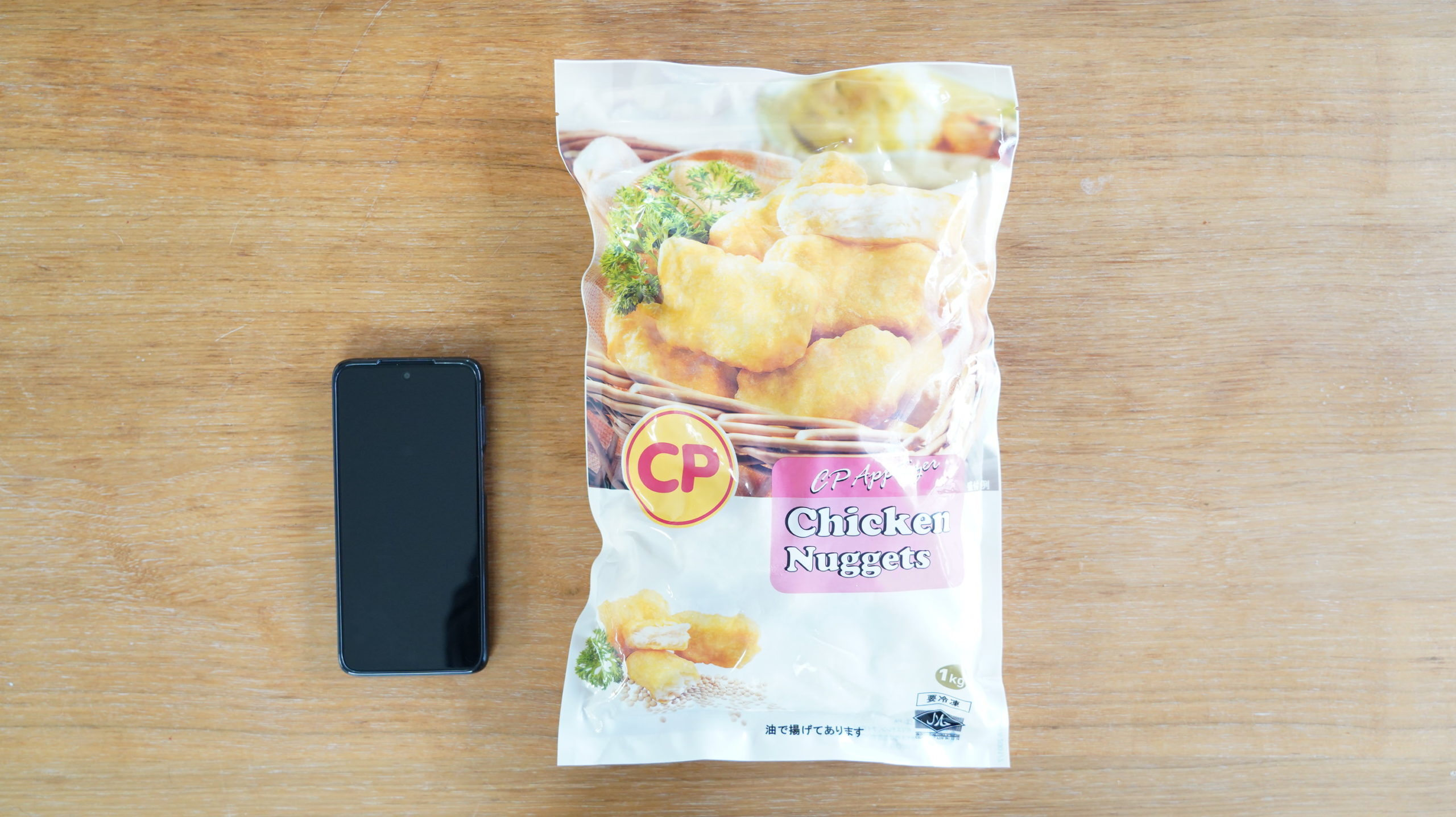 コストコの冷凍食品「CP チキンナゲット」とスマホの大きさを比較した写真