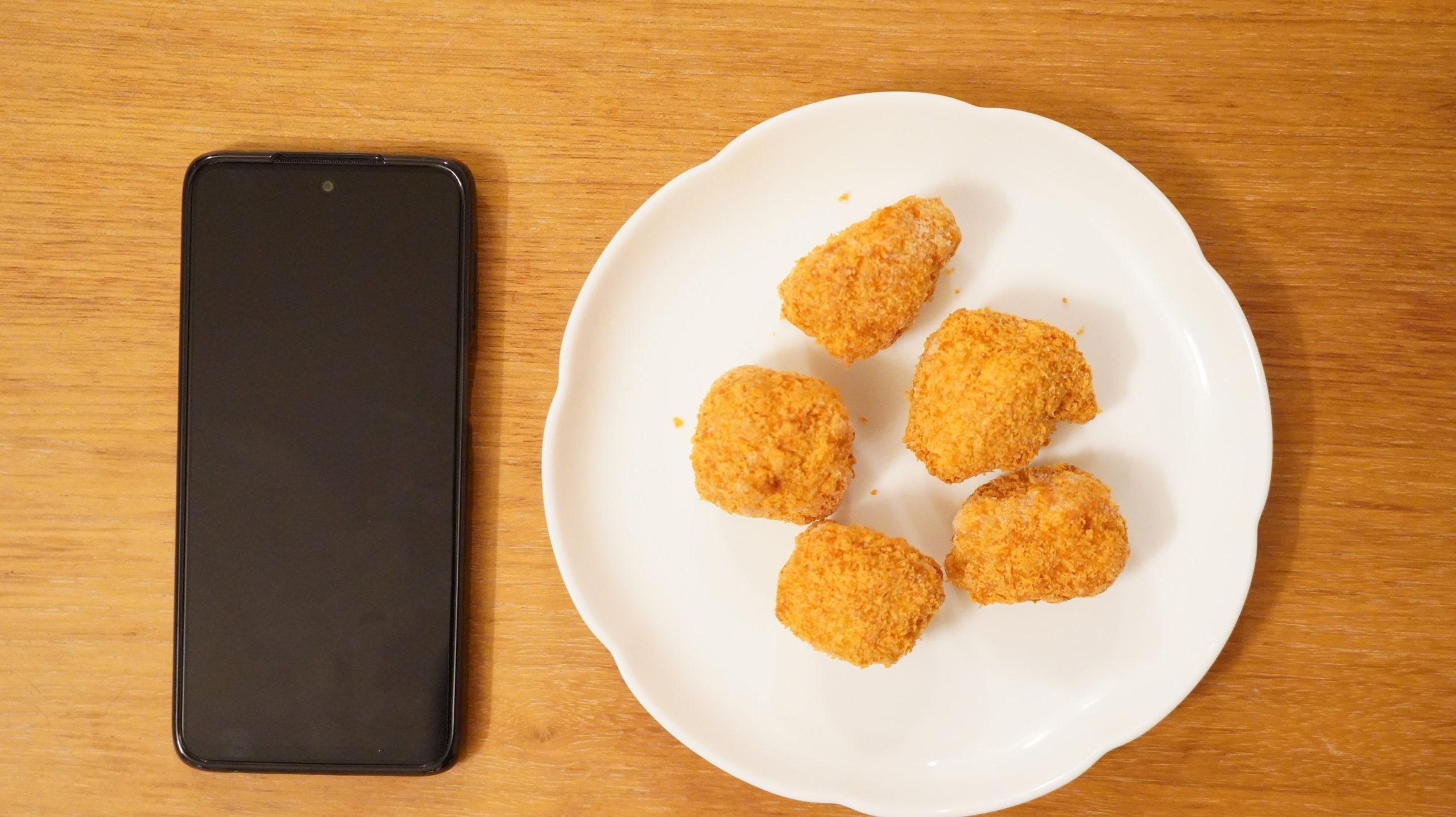 コストコの冷凍食品「味の素・三元豚のとんかつ」とスマホの大きさを比較した写真