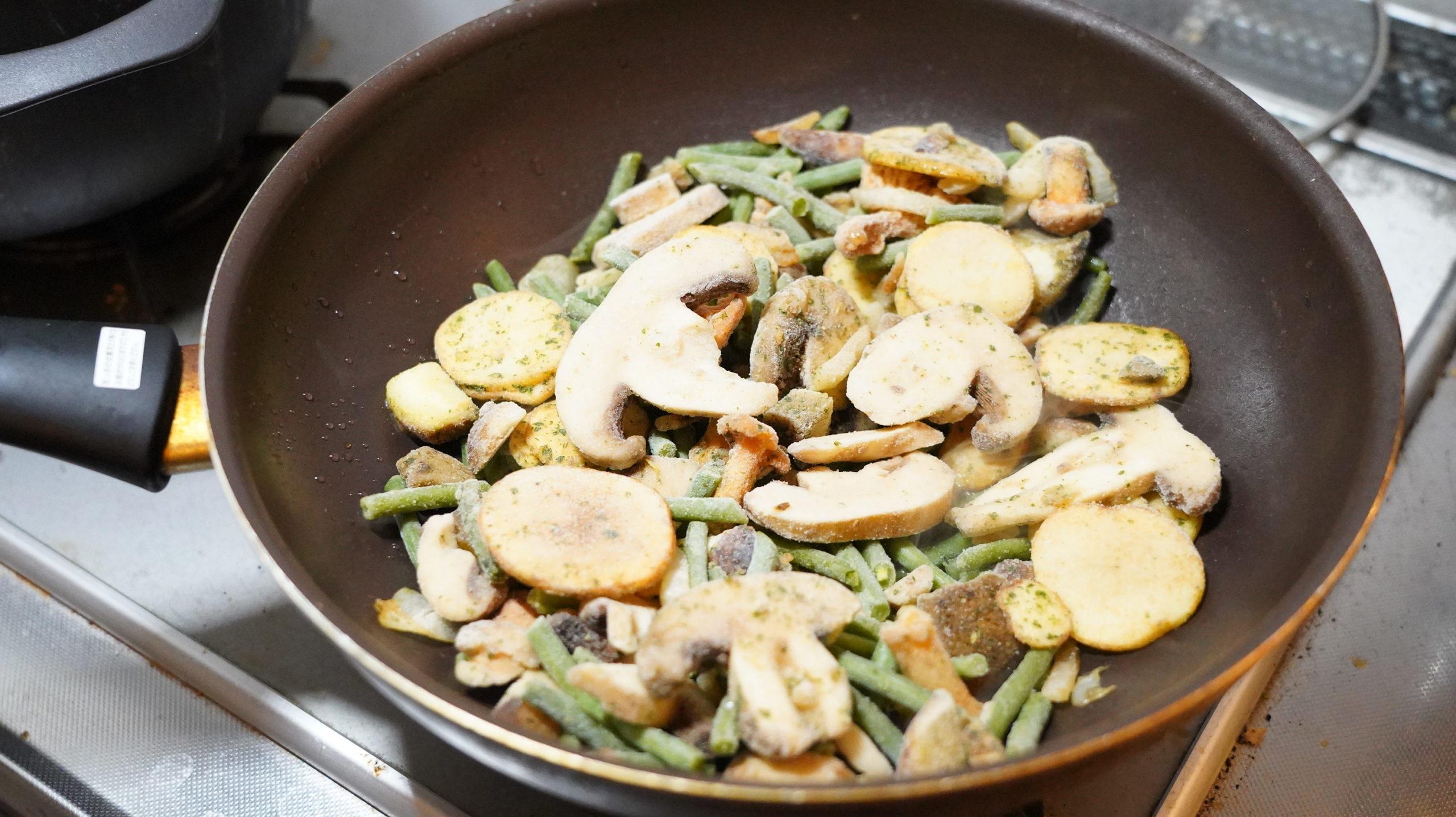 ピカールの冷凍食品「付合せ野菜ミックス(ジャガイモ、インゲン、キノコ)」をフライパンに乗せた写真
