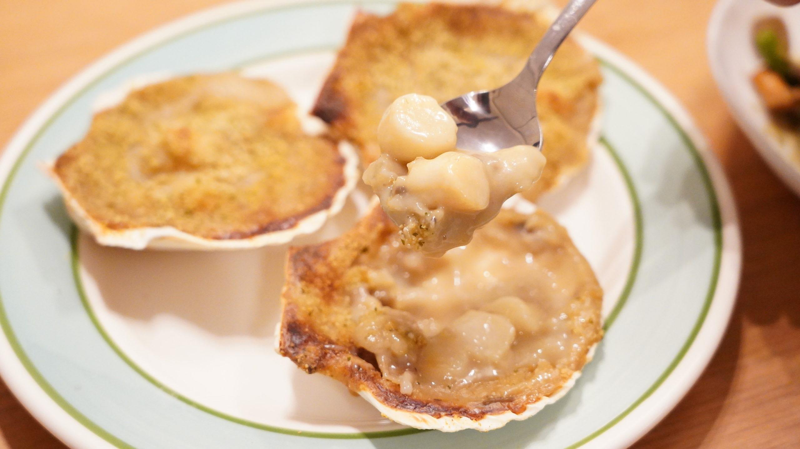ピカールの冷凍食品「サンジャックのオーブン焼き・ノルマンディ―風」をスプーンですくっている写真