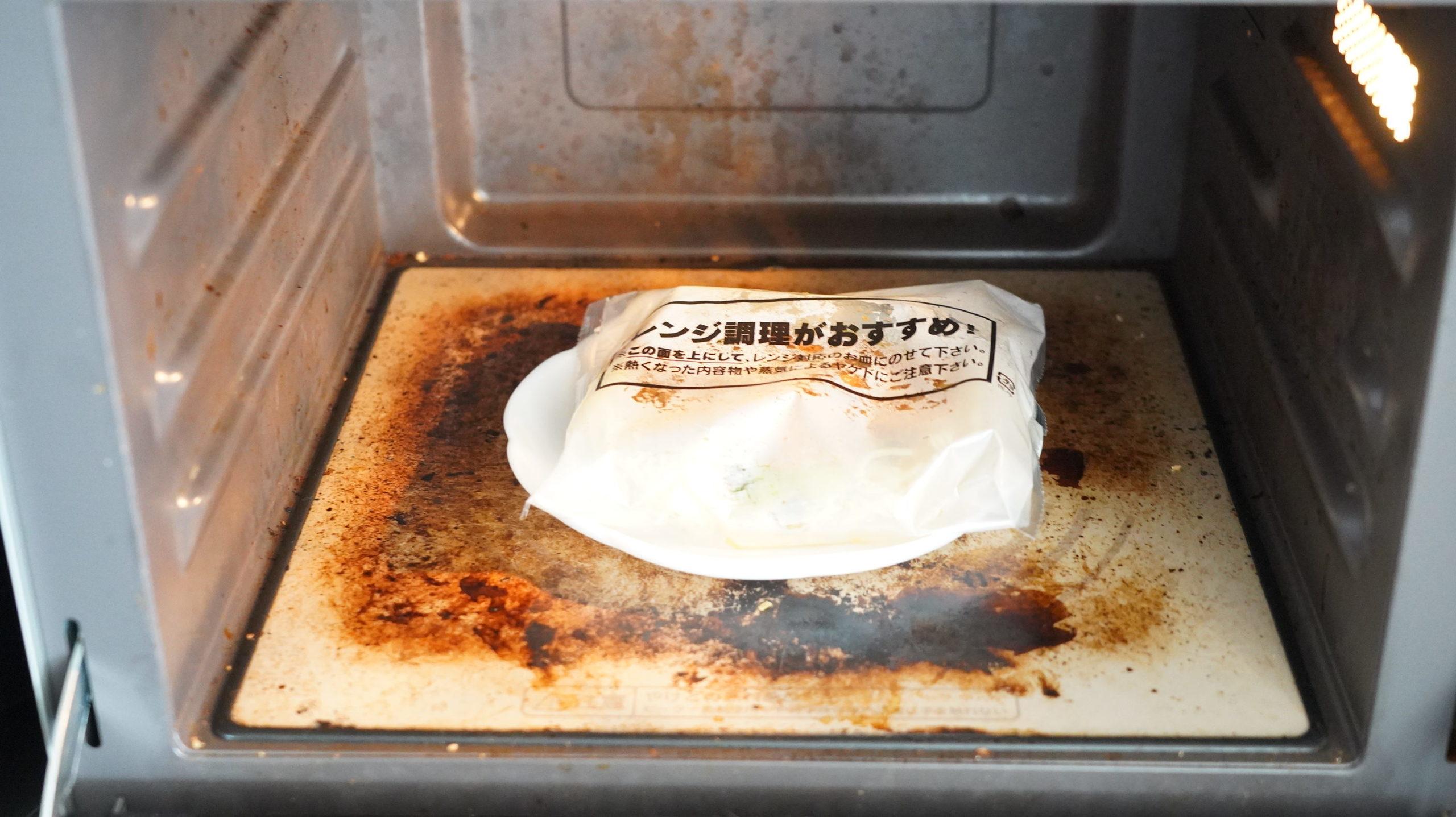 セブンイレブンの冷凍食品「胡麻が濃厚な坦々麺」の麺を電子レンジで加熱している写真