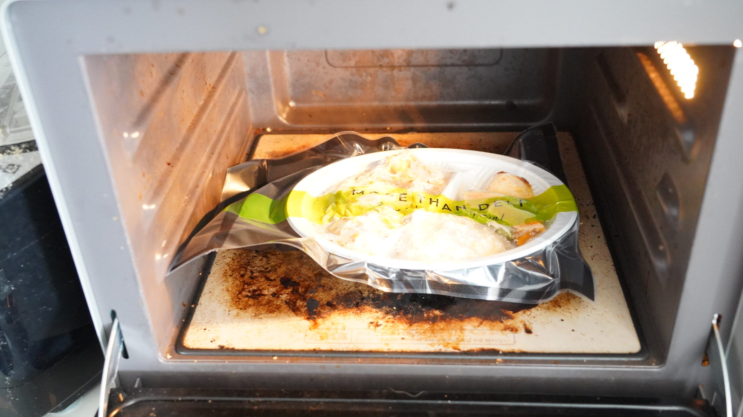 More than Deli(モアザンデリ)の冷凍弁当「鶏むね肉の野菜たっぷりカレー」を電子レンジで加熱している写真