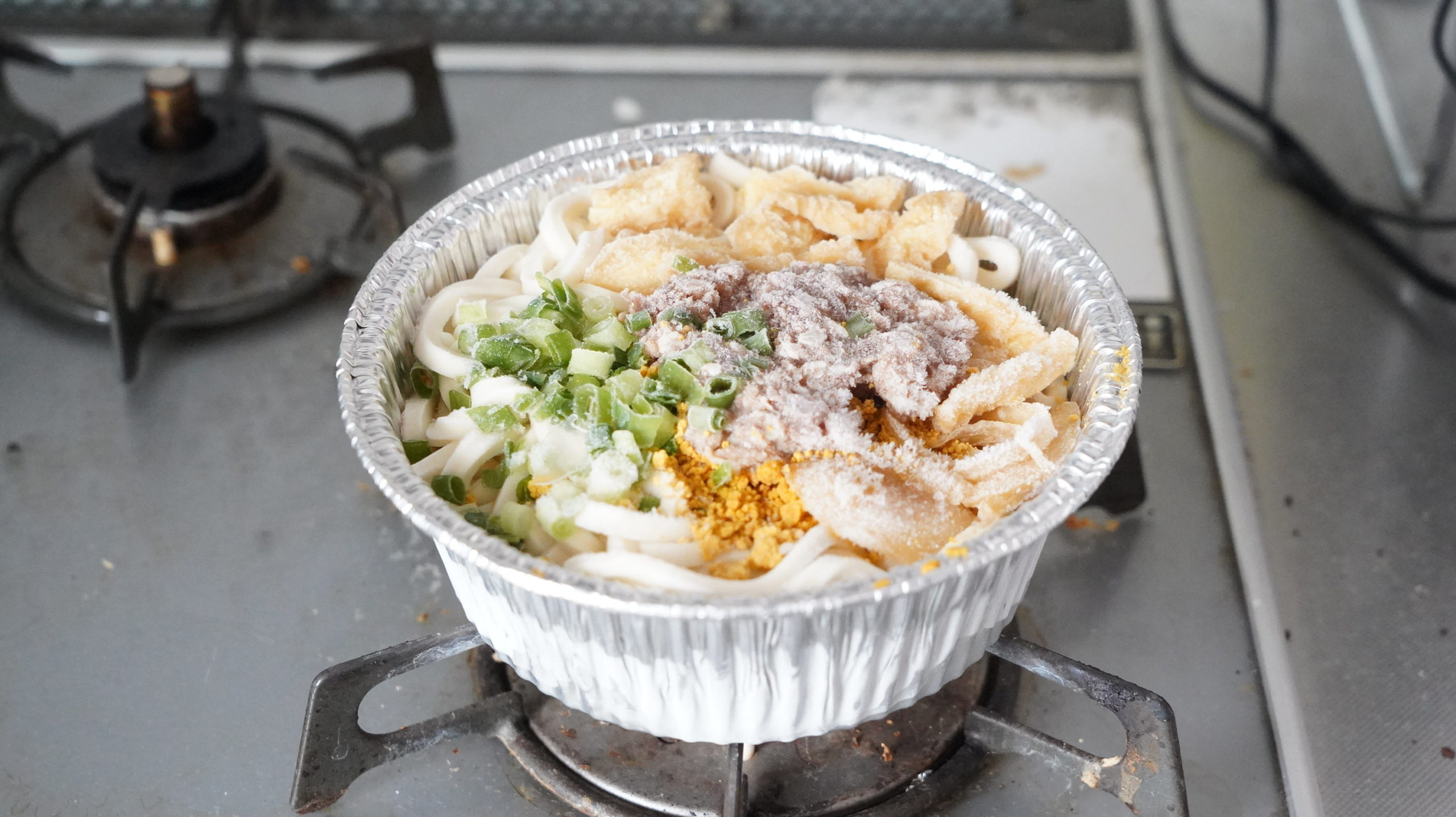 ファミリーマートの冷凍食品「和風だしのきいた牛肉カレーうどん」をガスコンロで加熱している写真