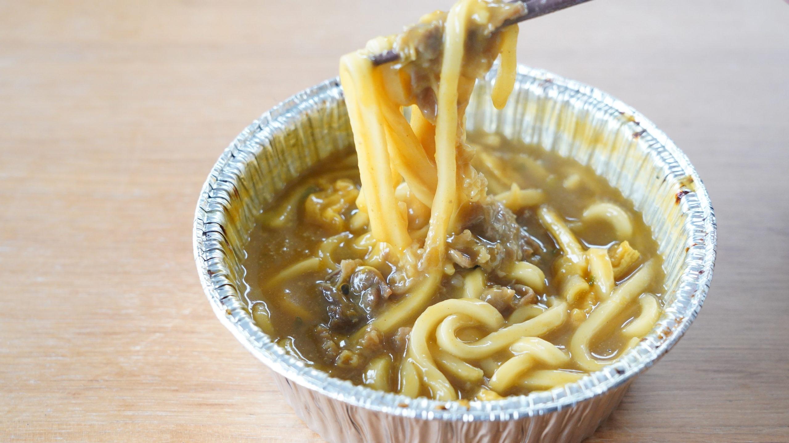 ファミリーマートの冷凍食品「和風だしのきいた牛肉カレーうどん」を箸でつまんでいる写真