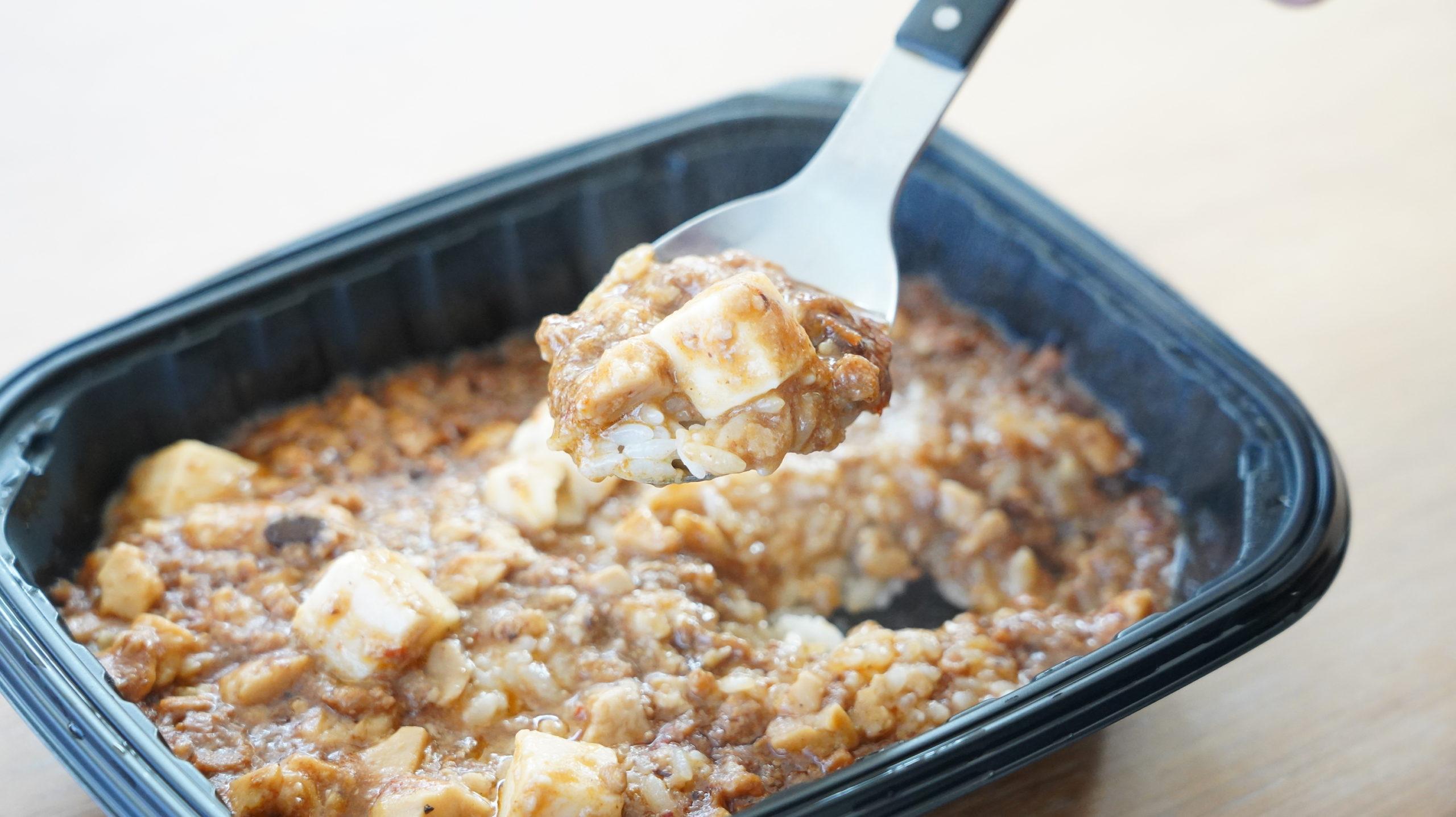 ファミリーマートの冷凍食品「花椒香る四川風麻婆豆腐丼」をスプーンですくっている写真