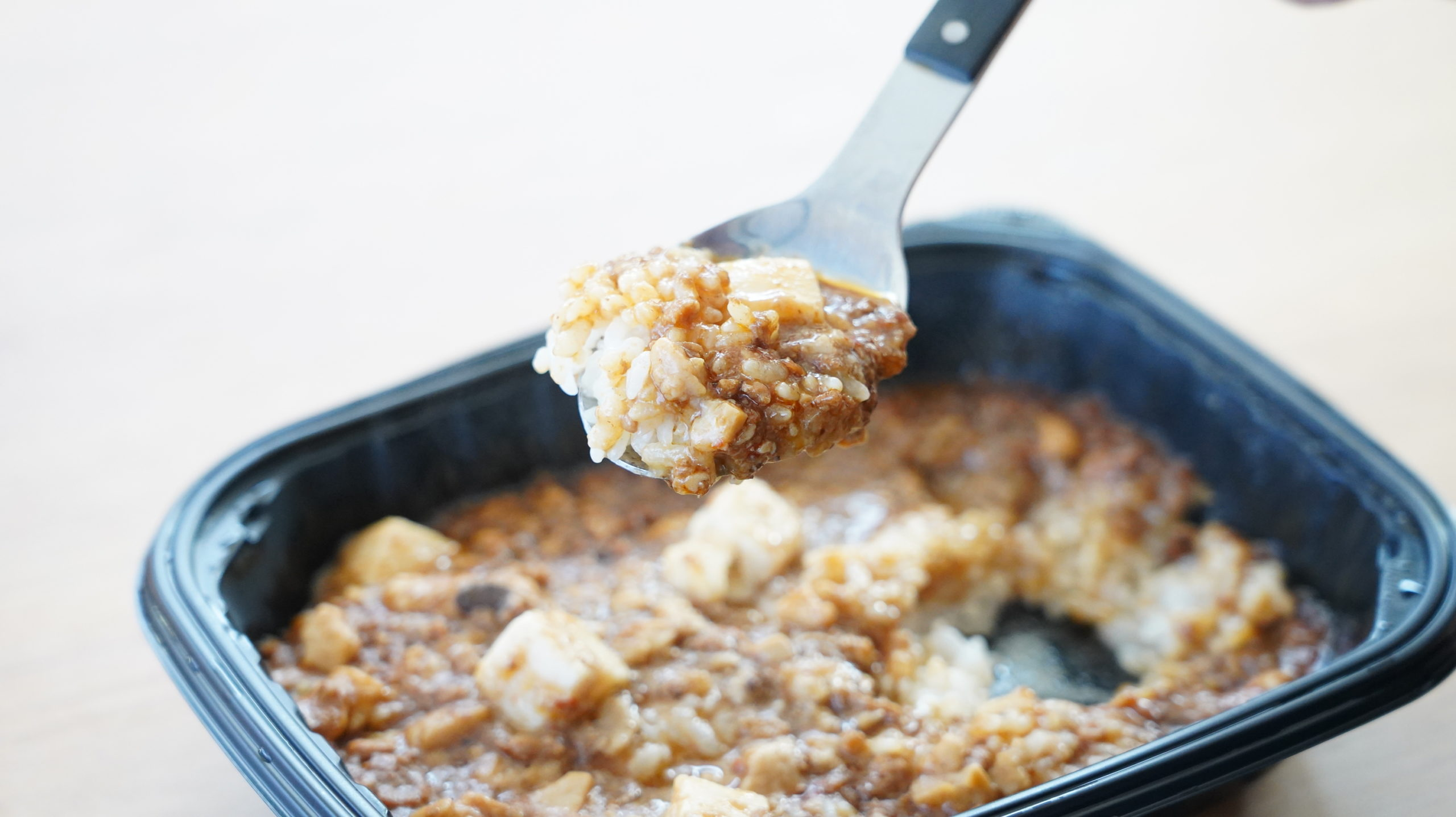 ファミリーマートの冷凍食品「花椒香る四川風麻婆豆腐丼」の豆腐とひき肉をスプーンですくっている写真