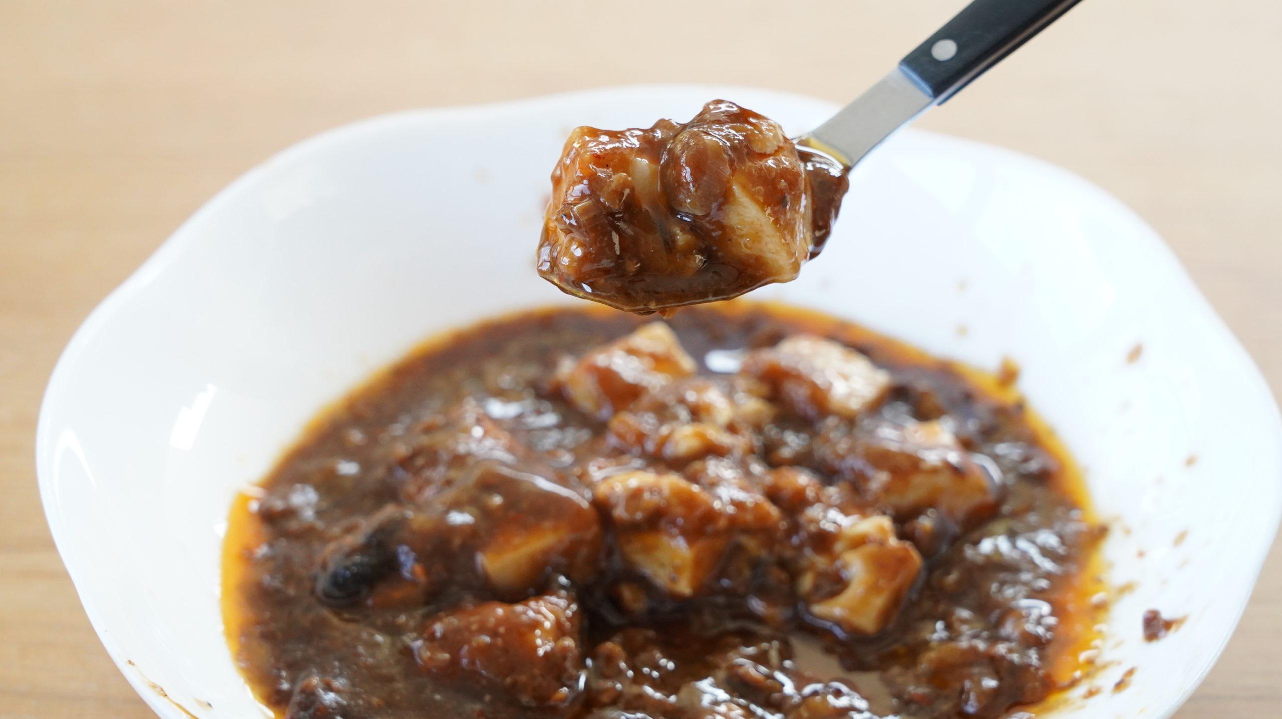 ローソンの冷凍食品「四川風麻婆豆腐」の麻婆豆腐をスプーンですくっている写真