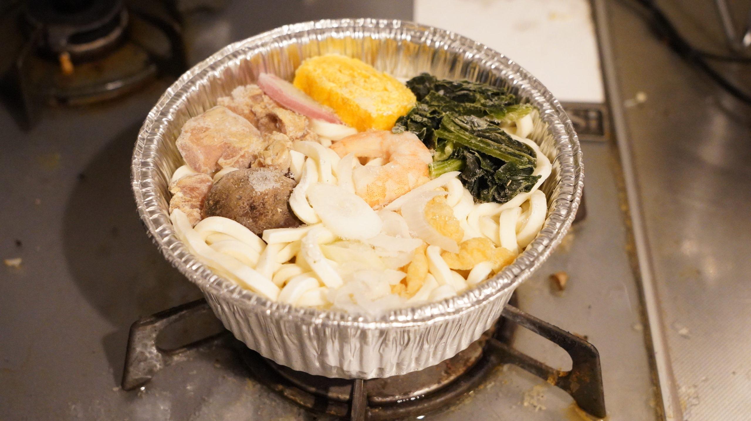 ファミリーマートの冷凍食品「だしが自慢の鍋焼うどん」をガスコンロで加熱している写真