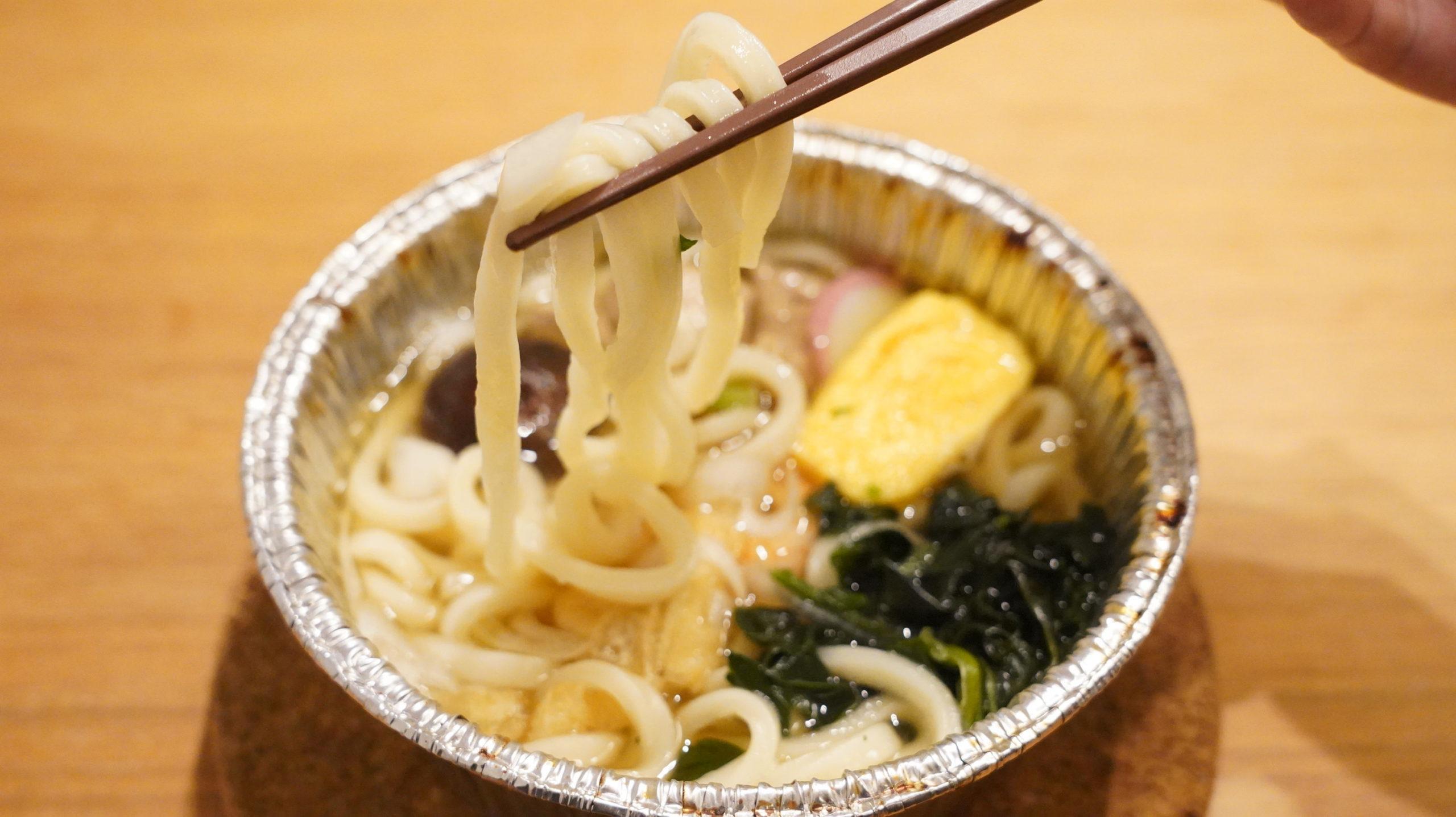 ファミリーマートの冷凍食品「だしが自慢の鍋焼うどん」を箸で持ち上げている写真
