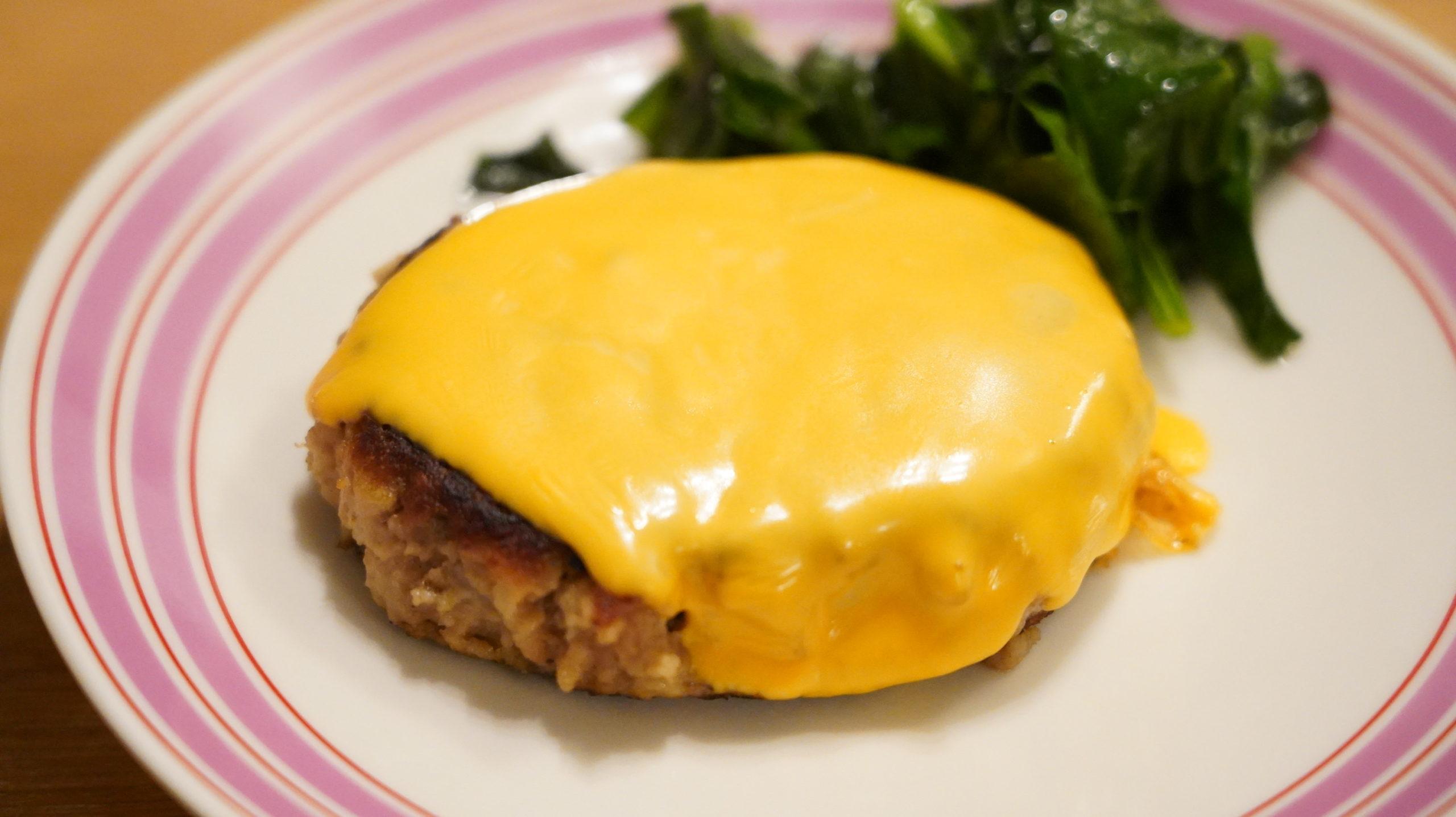 業務スーパーの冷凍食品「あらびきハンバーグ」にチェダーチーズを乗せた写真