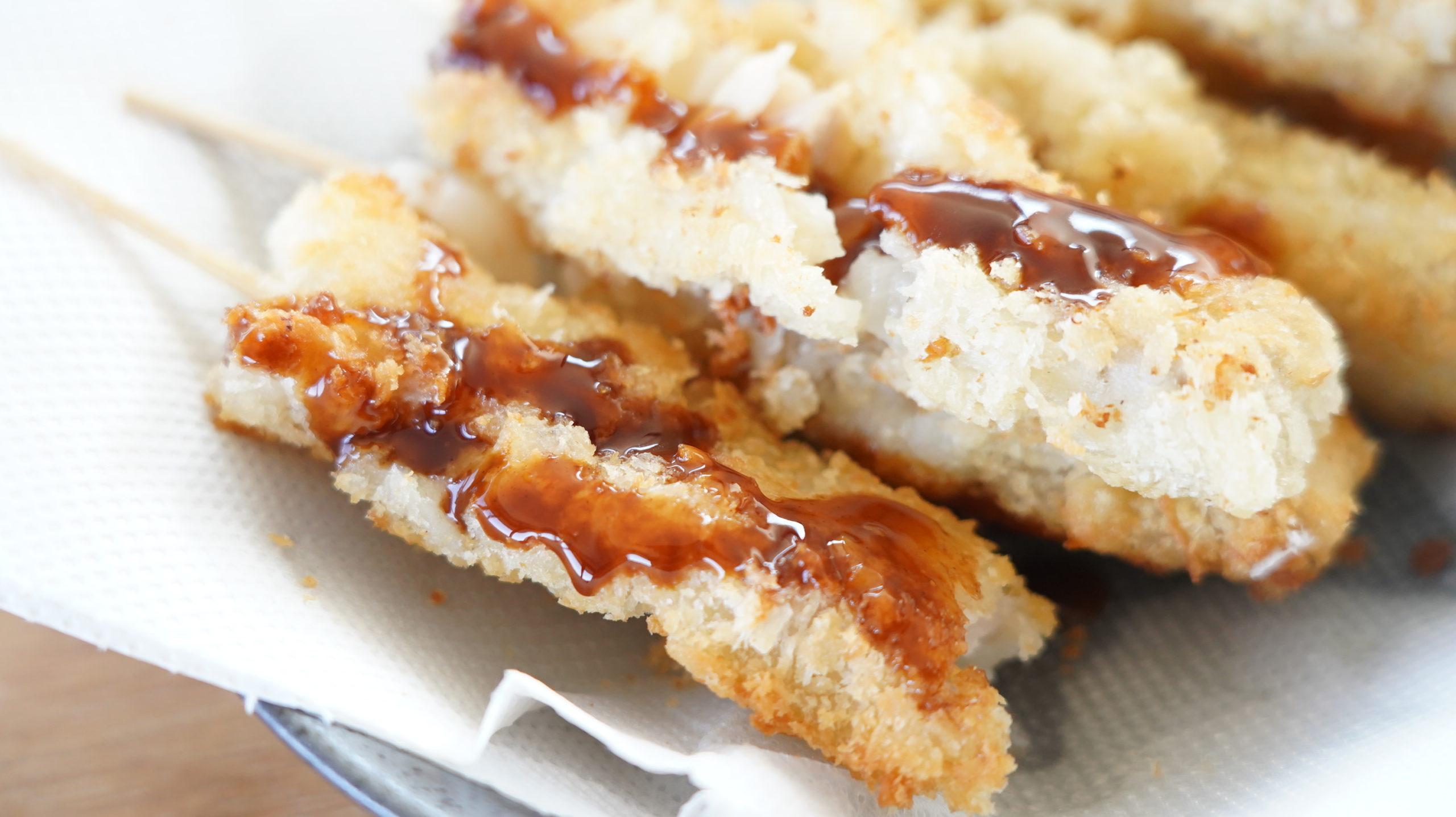 業務スーパーの冷凍食品「豚たまねぎ串カツ」にソースをかけた写真