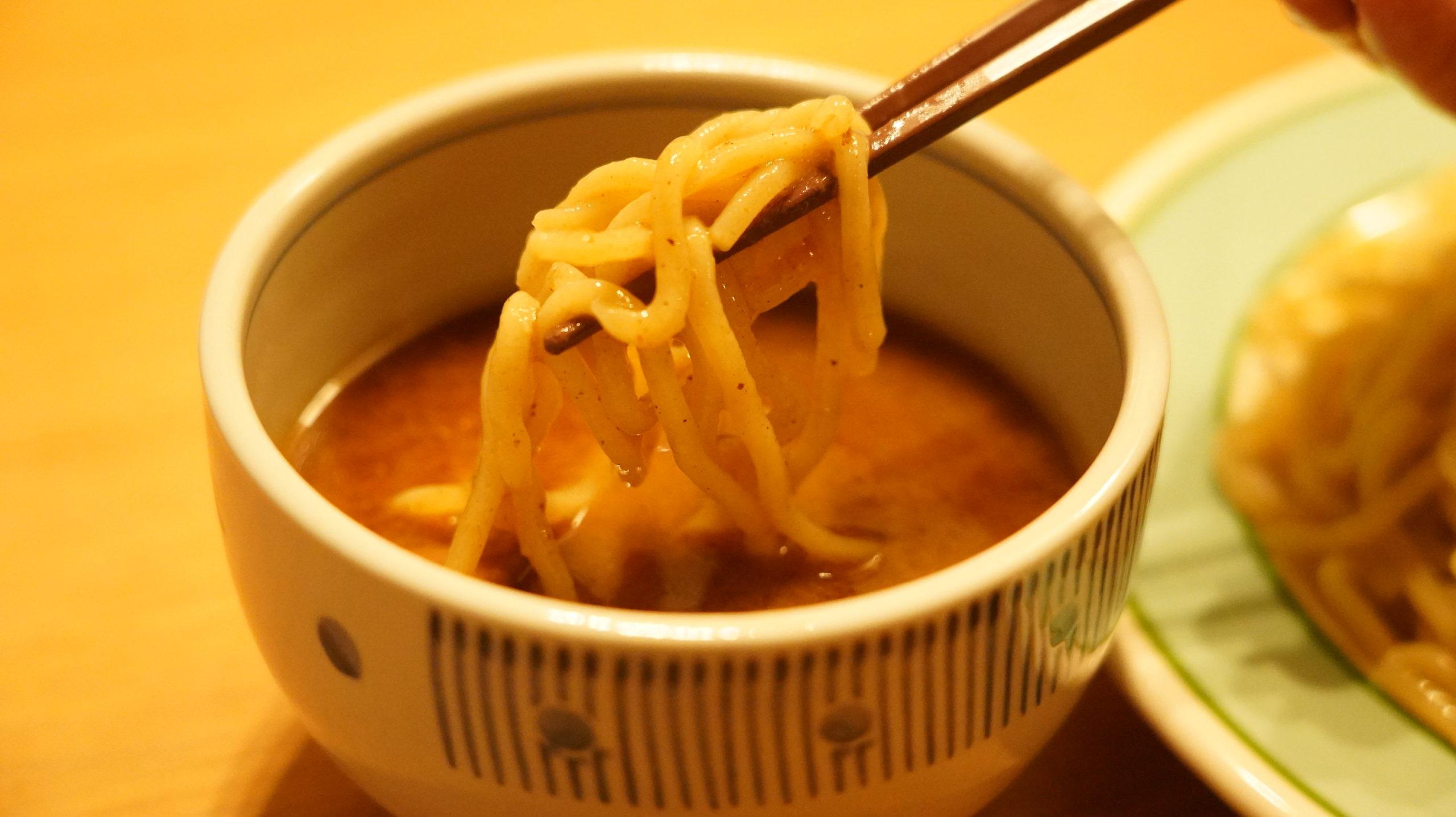 オンライン通販で注文した三田製麺所の「冷凍つけ麺」の麺を箸でつまんでいる写真