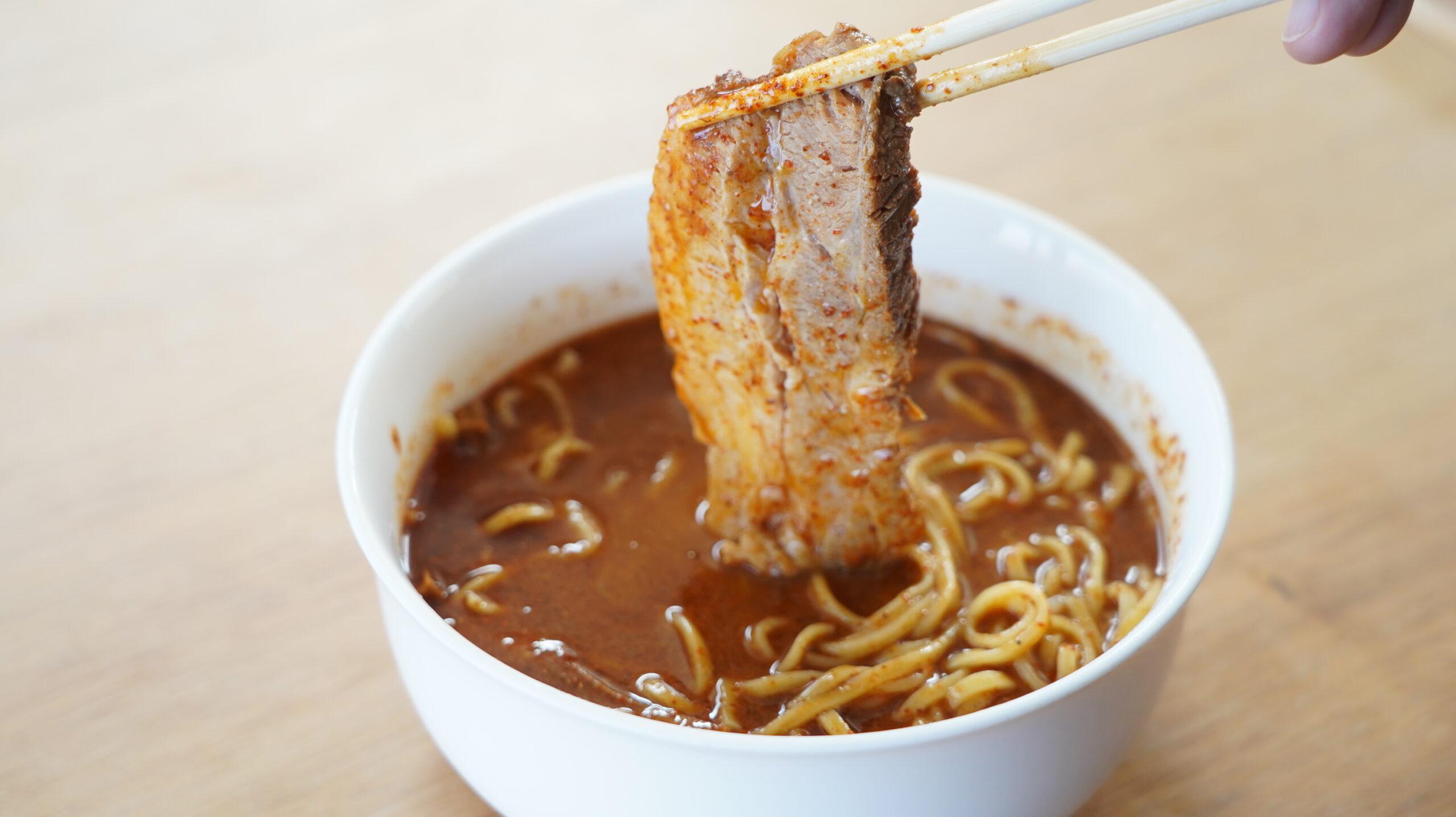 麺処「井の庄」のお取り寄せ・オンライン通販用「辛辛魚らーめん」のチャーシューを箸でつまんでいる写真
