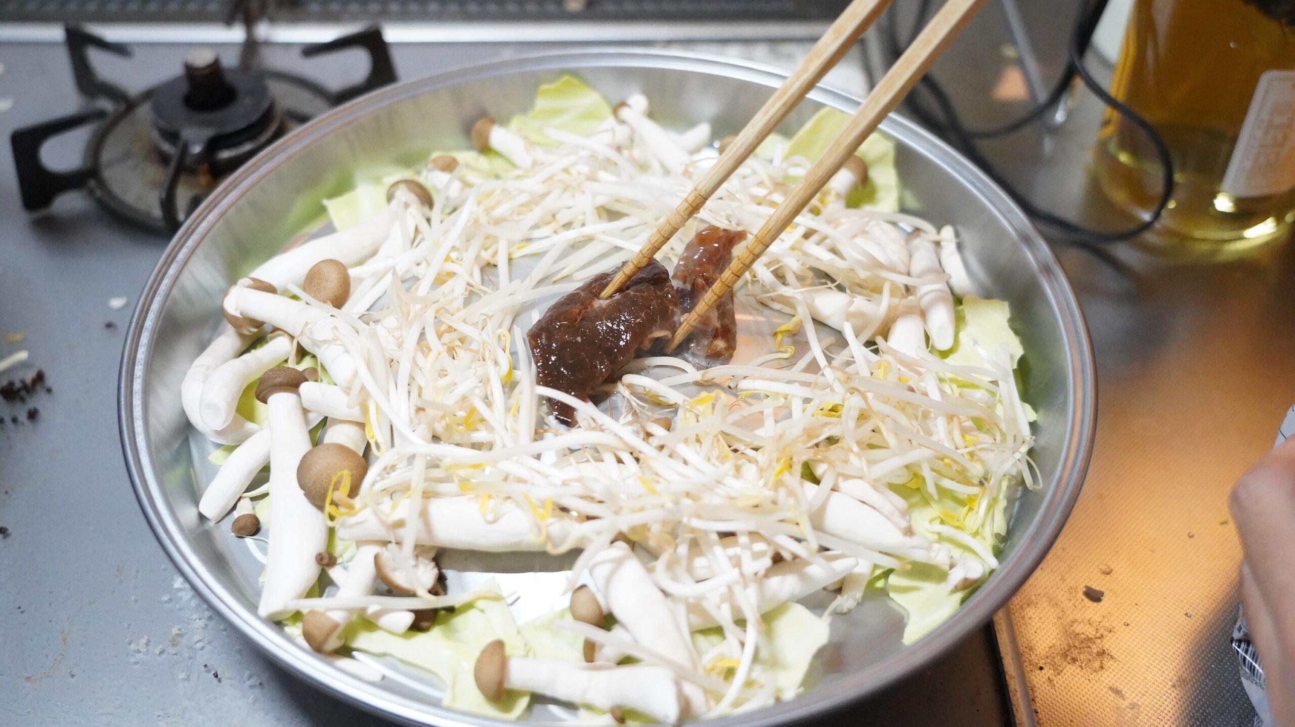 松尾ジンギスカンを通販でお取り寄せした冷凍マトン肉を専用の鍋で焼いている写真