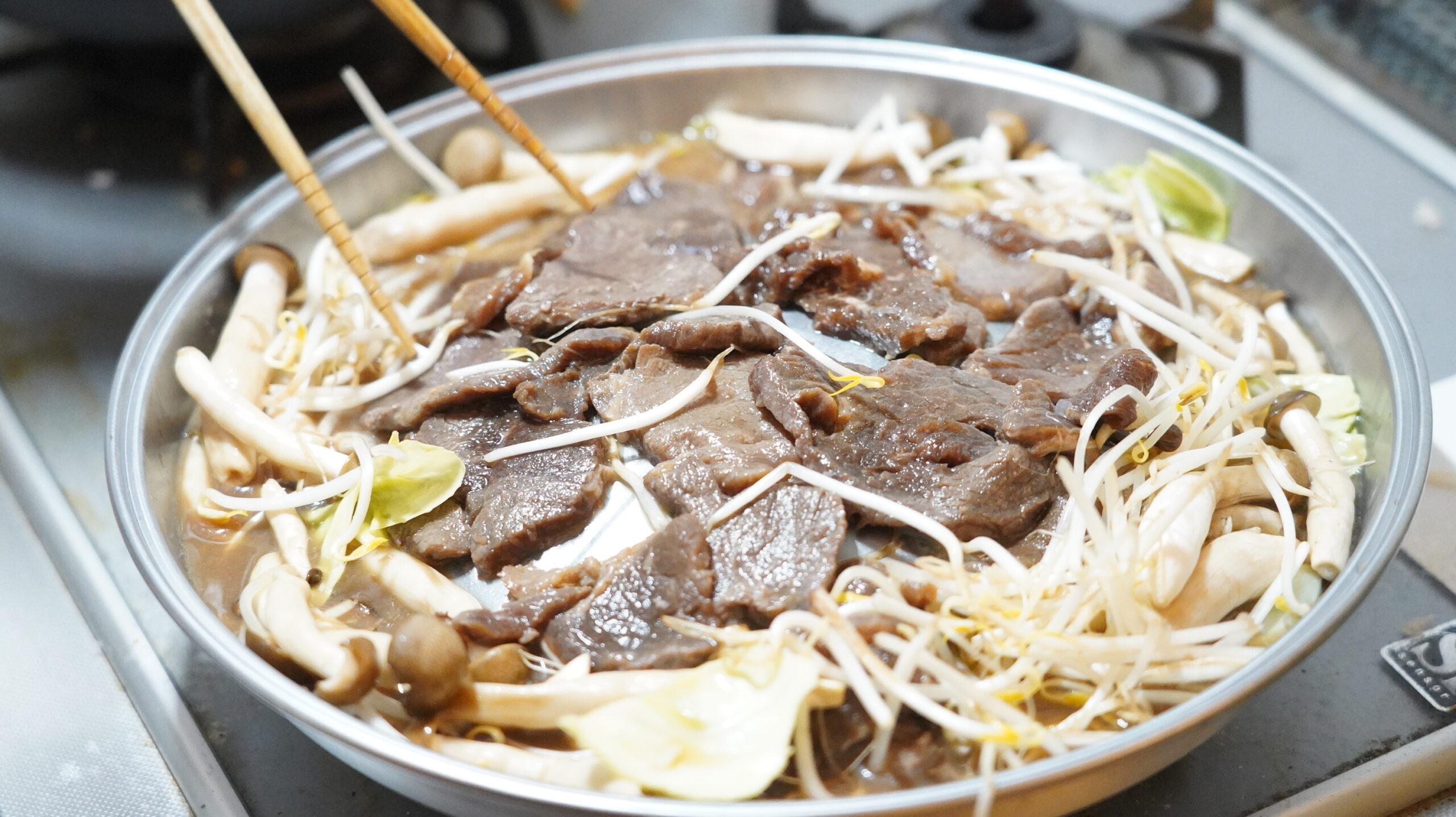 松尾ジンギスカンを通販でお取り寄せした冷凍マトン肉を箸で焼いている写真