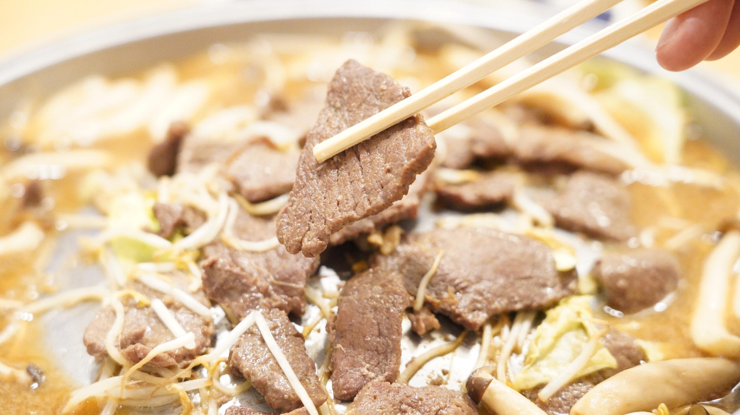 松尾ジンギスカンを通販でお取り寄せした冷凍マトン肉を箸でつまんでいる写真