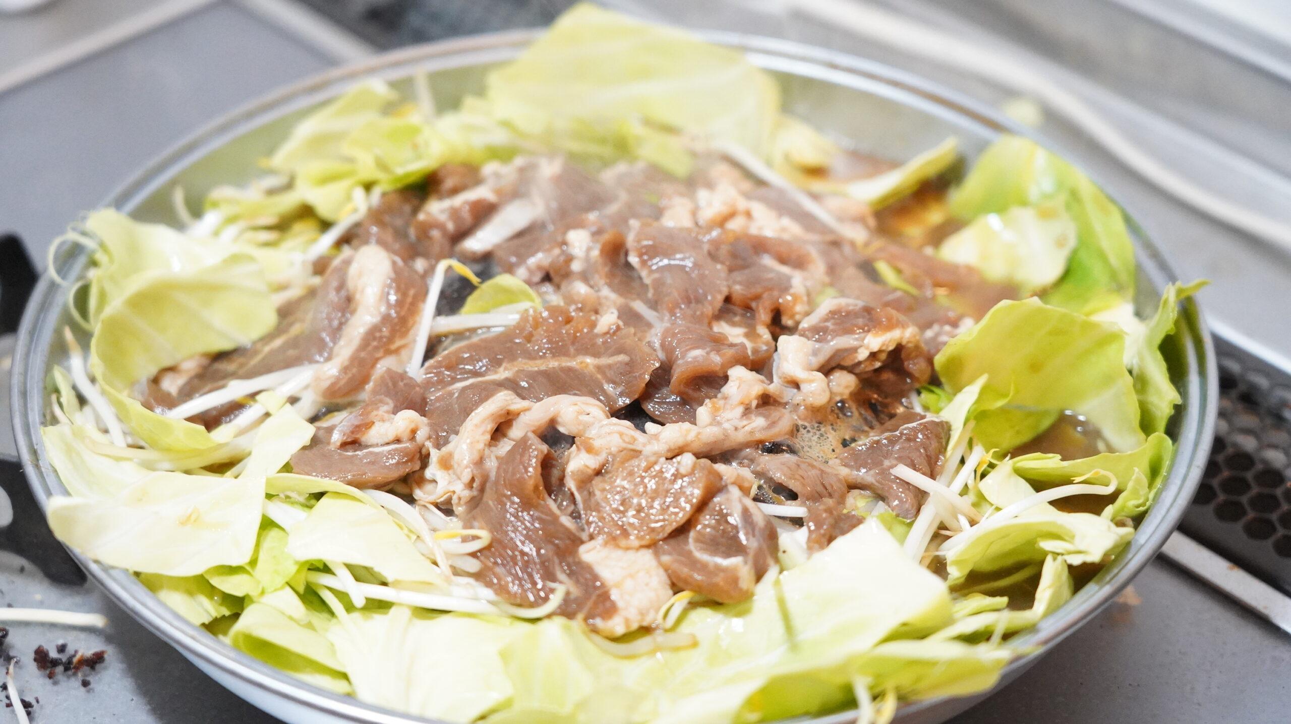 松尾ジンギスカンを通販でお取り寄せした冷凍マトン肉を野菜と一緒に焼いている写真