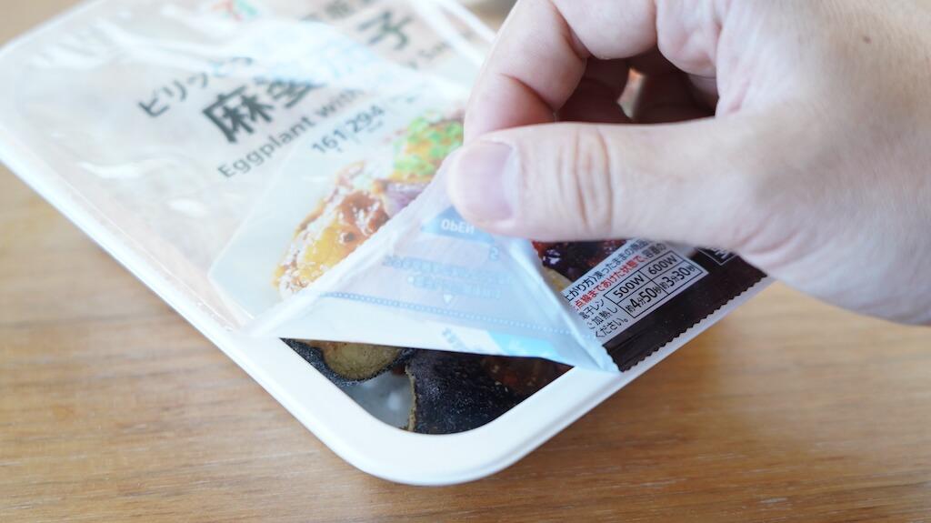 セブンイレブンの冷凍食品「ピリッとうま辛豆板醤の麻婆茄子」のフタを点線まであけている写真