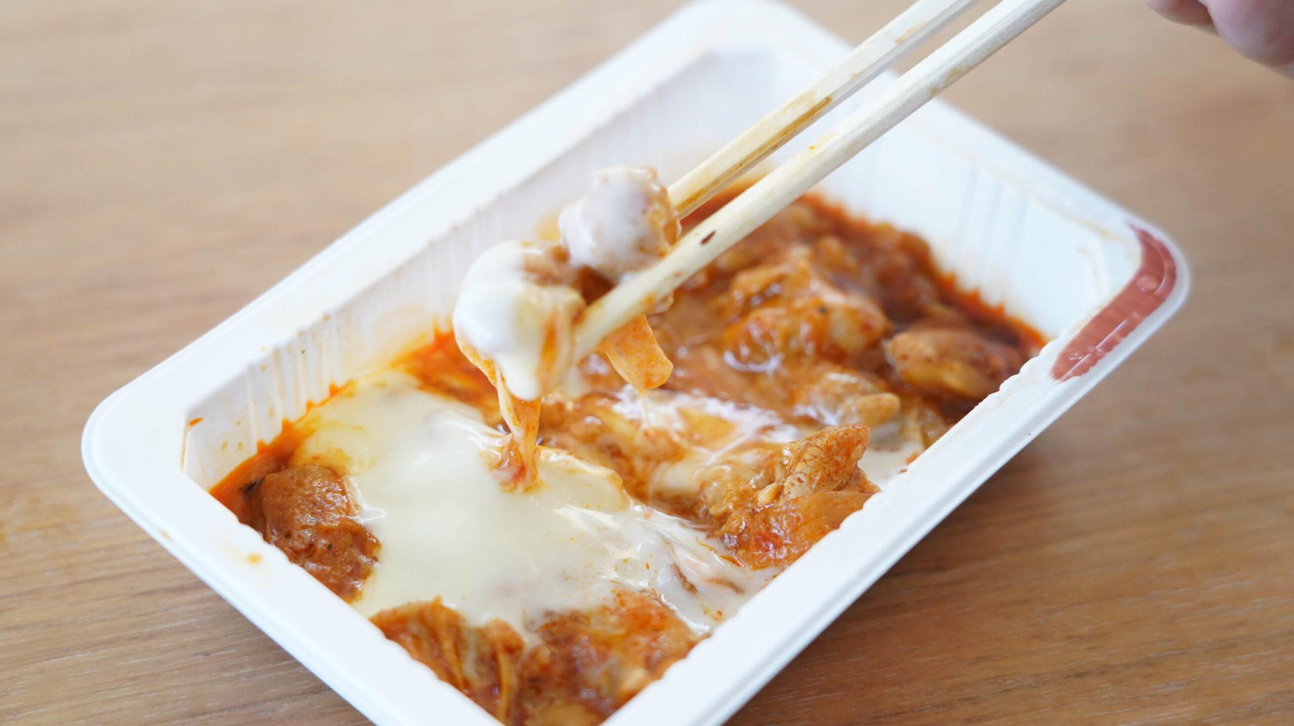 セブンイレブンの冷凍食品「とろけるチーズを絡めて・チーズダッカルビ」を箸でつまんでいる写真