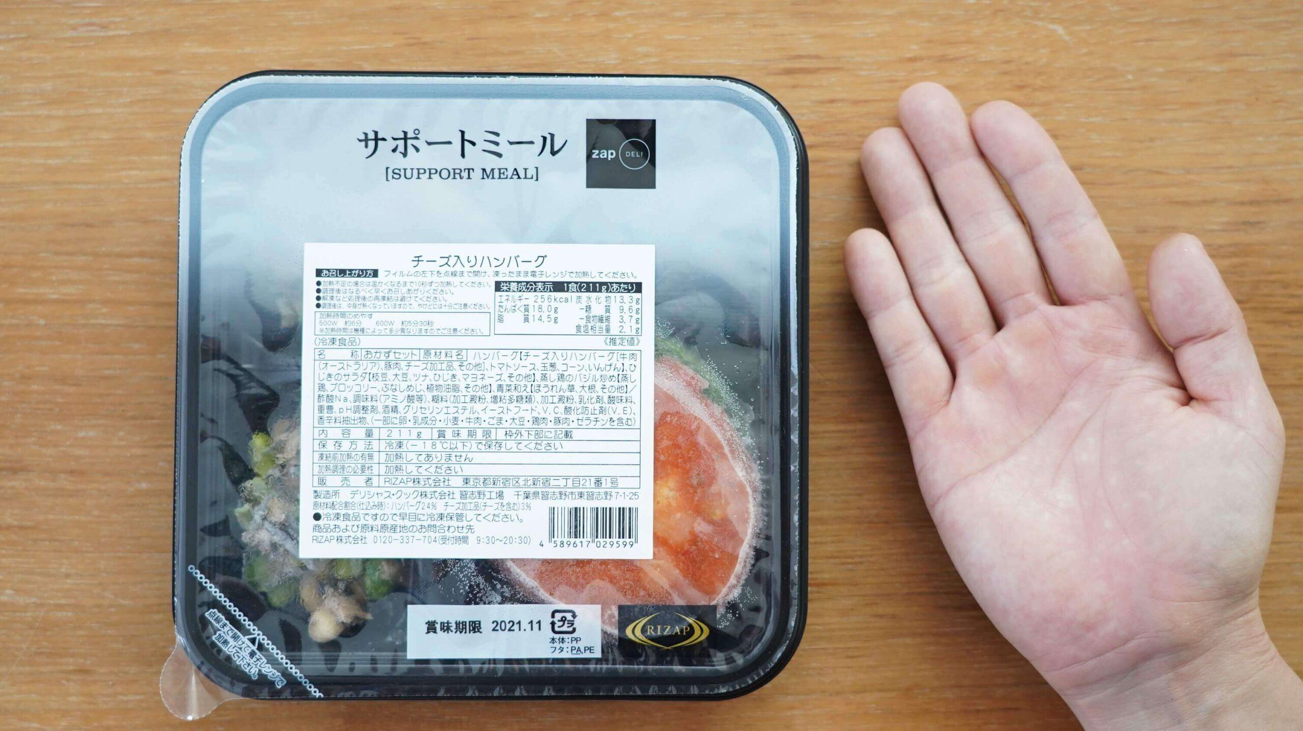 ライザップ(RIZAP)で食事制限してダイエットする際に使う宅食用ボディメイク冷凍弁当「サポートミール」(健康食品)と手のひらの大きさを比べている写真