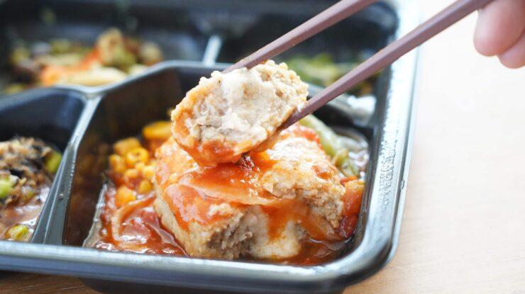 ライザップ(RIZAP)で食事制限してダイエットする際に使う宅食用ボディメイク冷凍弁当「サポートミール」(健康食品)の「チーズ入りハンバーグ」を箸でつまんでいる写真