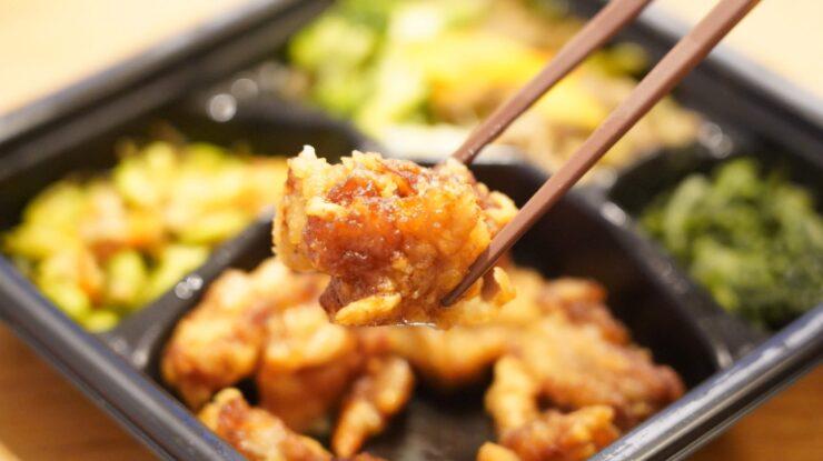 ライザップ(RIZAP)で食事制限してダイエットする際に使う宅食用ボディメイク冷凍弁当「サポートミール」(健康食品)の「鶏の唐揚げ」を箸でつまんでいる写真