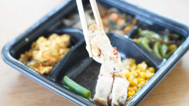 ライザップ(RIZAP)で食事制限してダイエットする際に使う宅食用ボディメイク冷凍弁当「サポートミール」(健康食品)の「鶏肉のエスニック焼き」を箸でつまんでいる写真