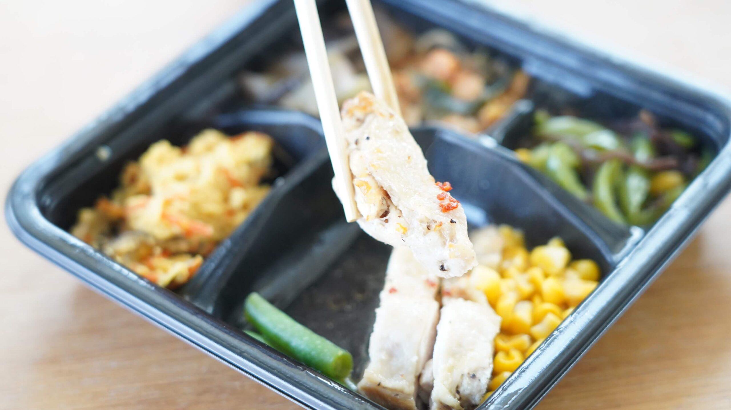 ライザップのサポートミール「鶏肉のエスニック焼き」の「鶏肉のエスニック焼き」を箸でつまんだ写真