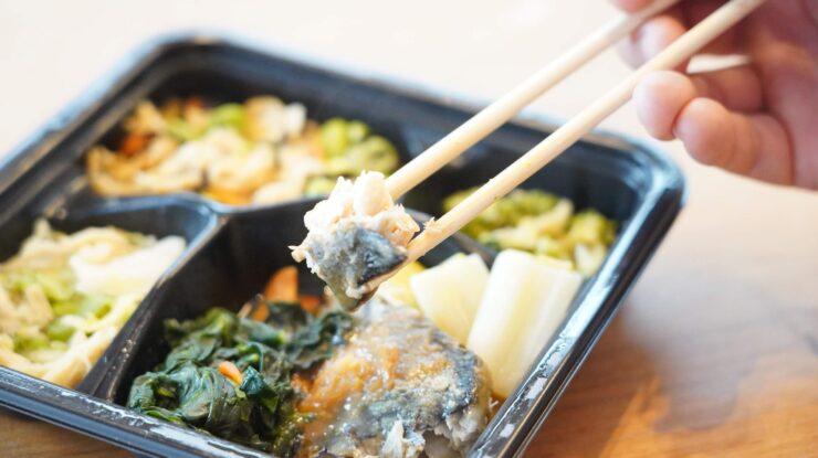 ライザップ(RIZAP)で食事制限してダイエットする際に使う宅食用ボディメイク冷凍弁当「サポートミール」(健康食品)の「さばの味噌煮」を箸でつまんでいる写真