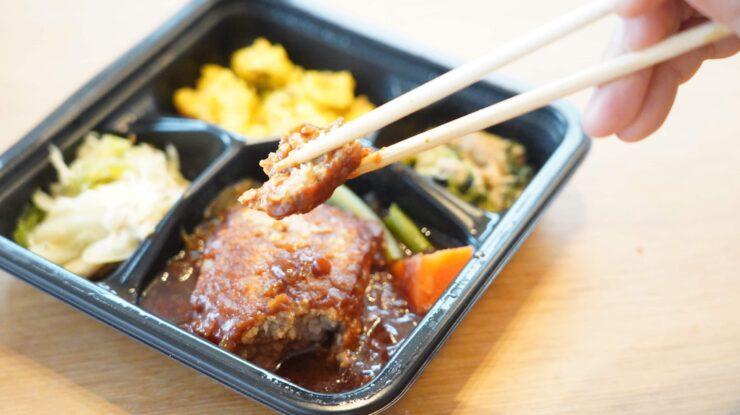 ライザップ(RIZAP)で食事制限してダイエットする際に使う宅食用ボディメイク冷凍弁当「サポートミール」(健康食品)の「デミグラスソースハンバーグ」を箸でつまんでいる写真