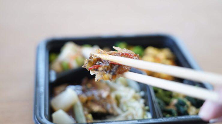ライザップ(RIZAP)で食事制限してダイエットする際に使う宅食用ボディメイク冷凍弁当「サポートミール」(健康食品)の「さんまの竜田揚げ」を箸でつまんでいる写真