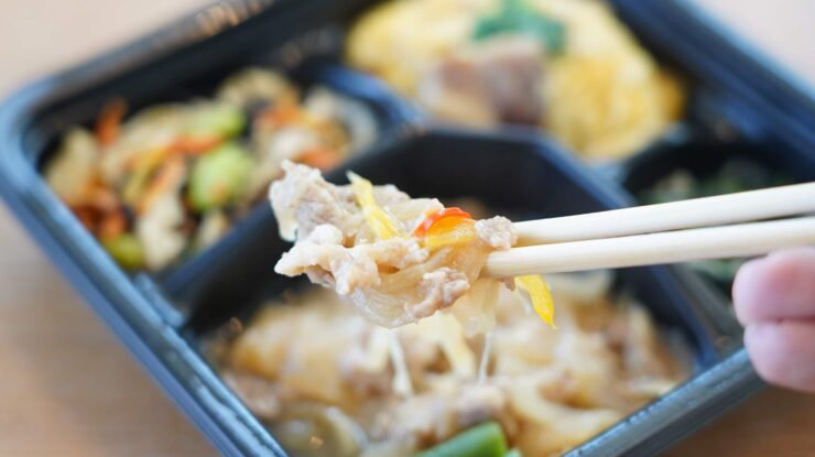 ライザップ(RIZAP)で食事制限してダイエットする際に使う宅食用ボディメイク冷凍弁当「サポートミール」(健康食品)の「豚の生姜焼き」を箸でつまんでいる写真