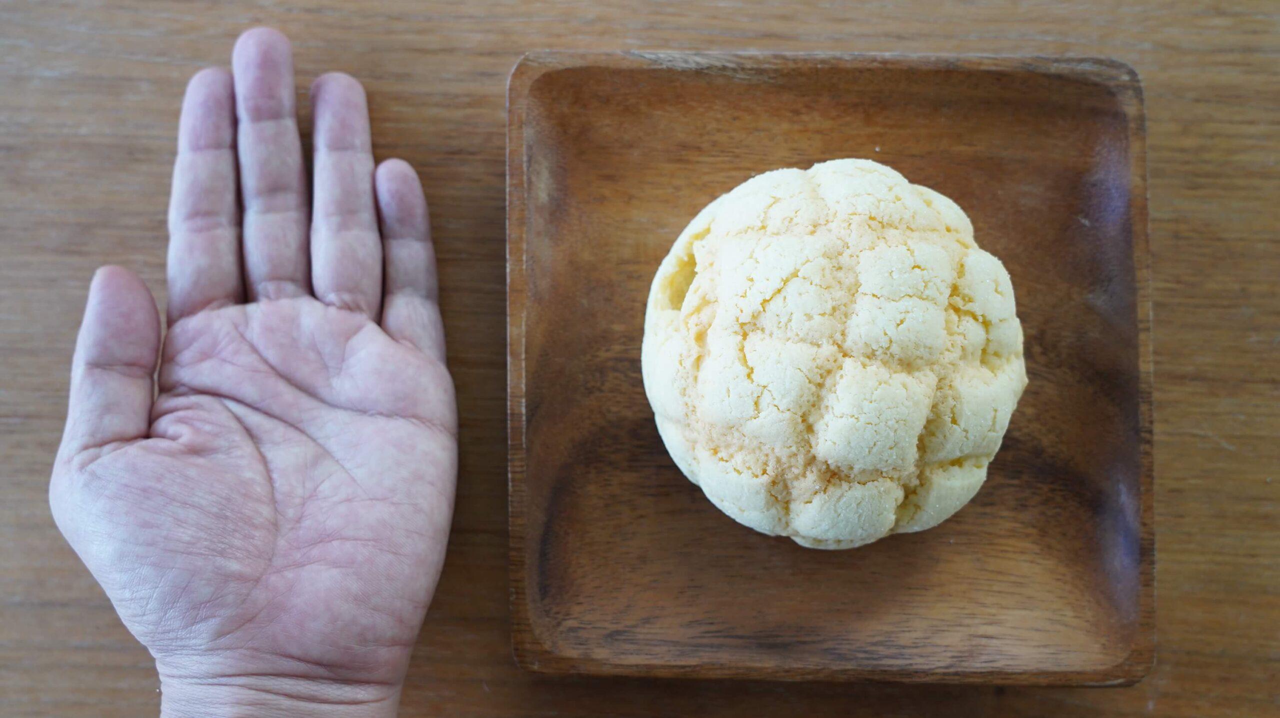 セブンイレブンの冷凍食品「冷たく食べるメロンパン」と手の大きさを比べている写真