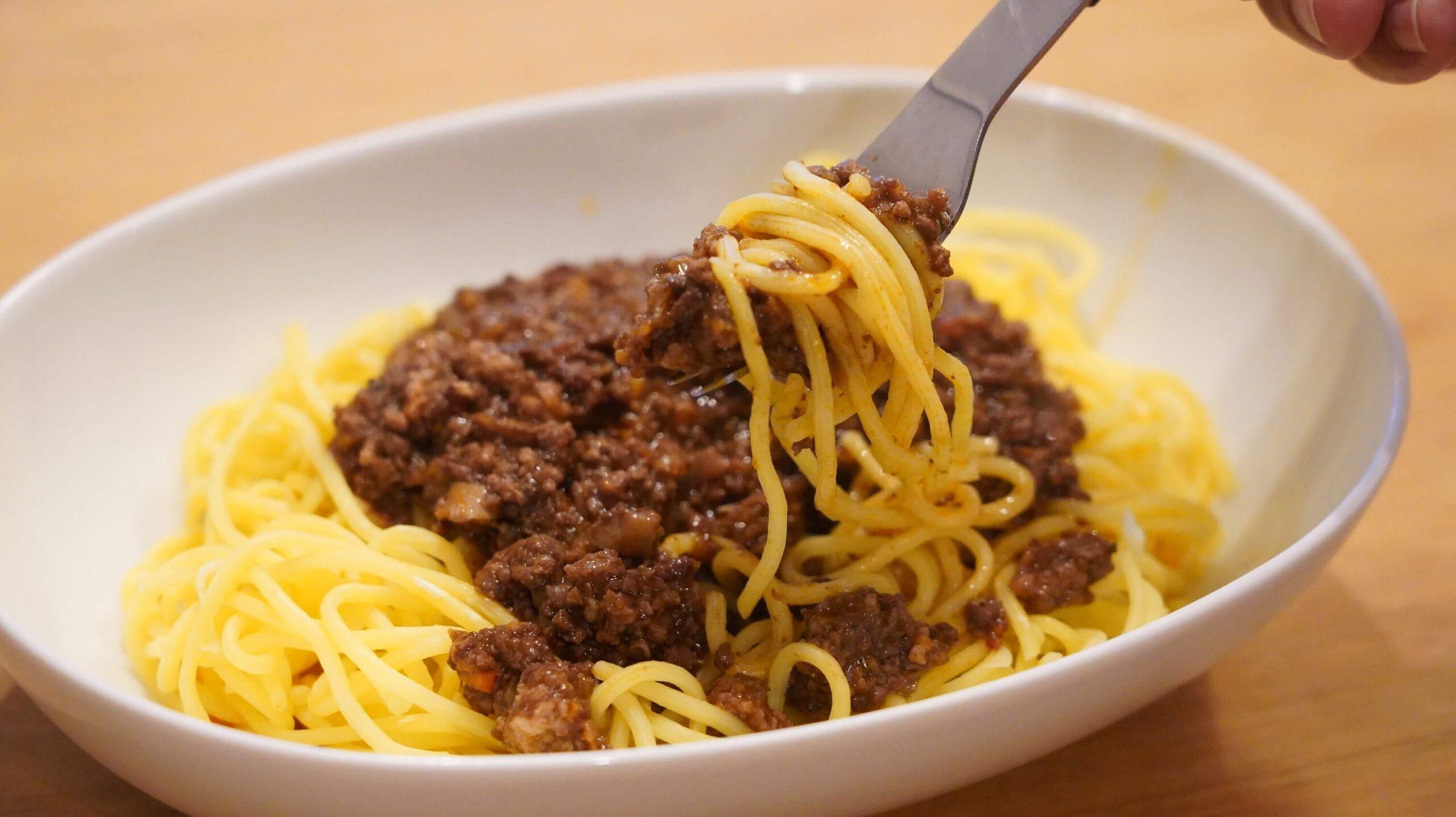 俺のイタリアンの冷凍食品「トリュフ薫るボロネーゼ」をフォークで持ち上げている写真